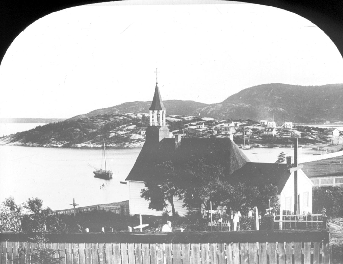 Une chapelle et son cimetière dominent une colline. Quelques maisons se trouvent sur la côte. Un bateau à voile est amarré.
