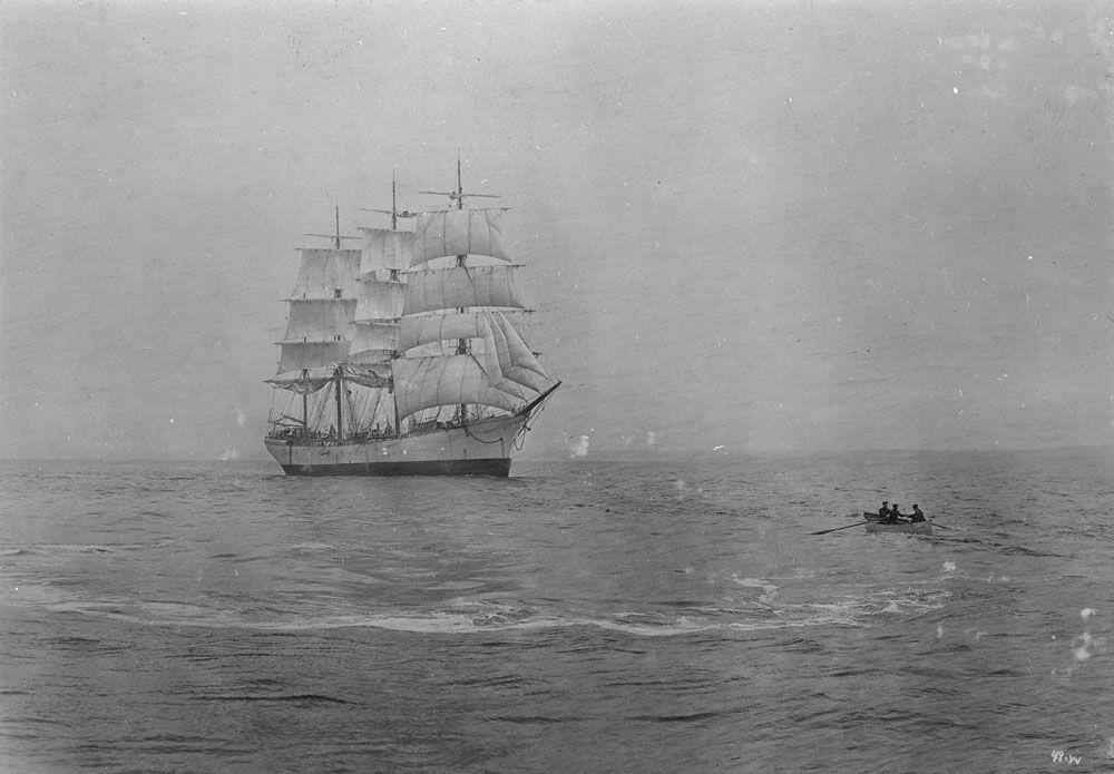Photographie ancienne en noir et blanc d'une petite embarcation qui se dirige vers un navire à voile