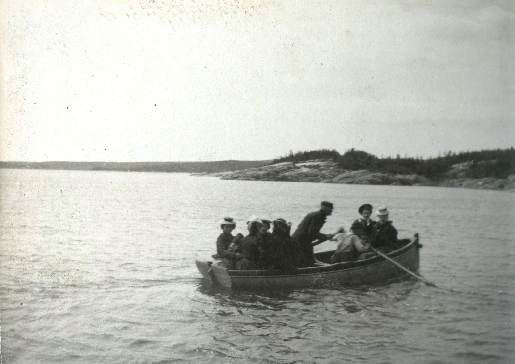Un homme rame dans une barque où se trouvent plusieurs estivants.