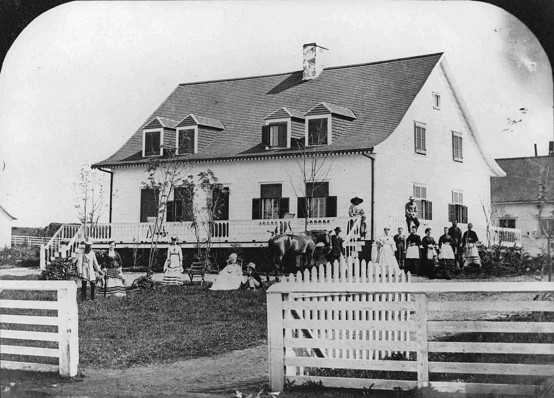 Un groupe d'une quinzaine de personnes pose devant une maison rurale ancienne.