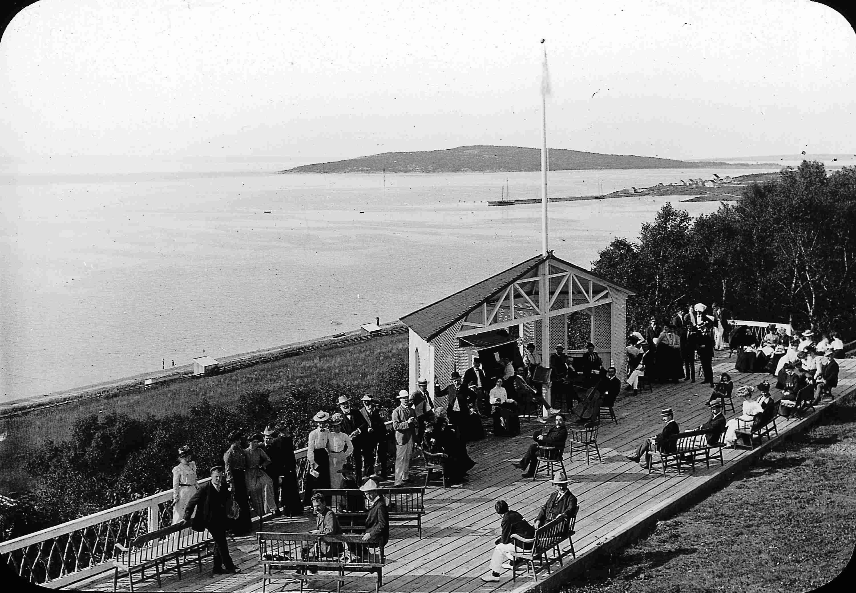 Des vacanciers discutent sur une terrasse en bois installée sur le flanc d'une falaise au bord de l'eau.