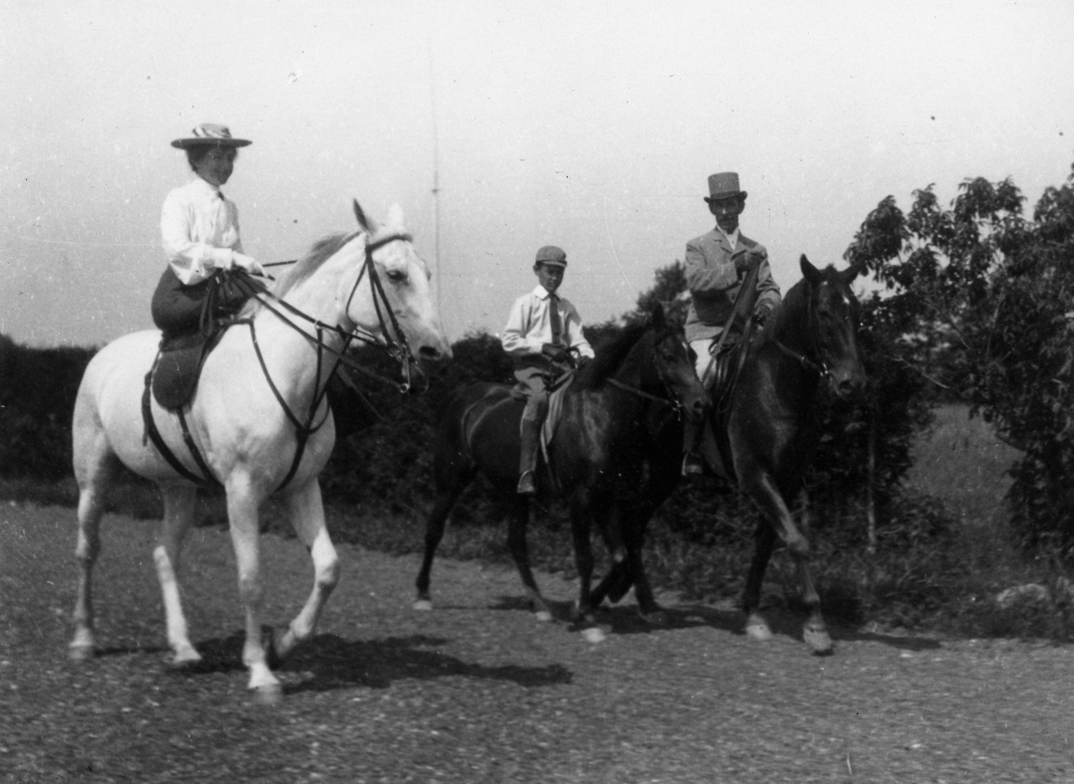 Trois cavaliers très élégants, dont une femme montée en amazone et un enfant, font une balade à cheval.