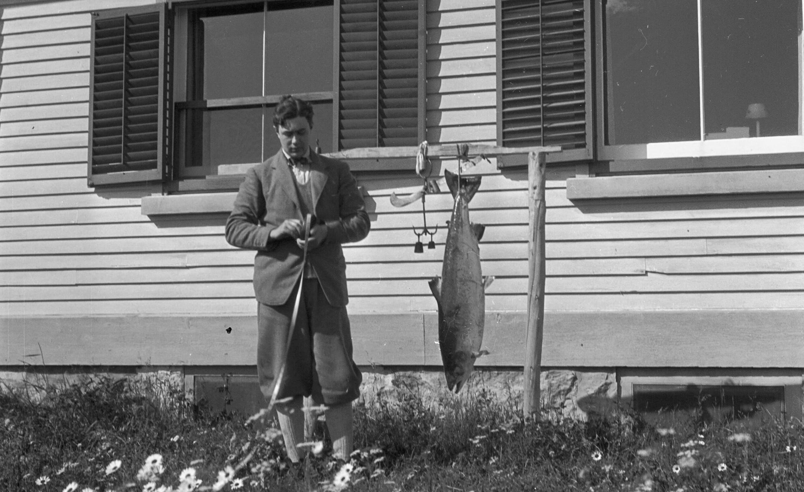 Un jeune homme range un ruban à mesurer près d'une installation extérieure pour la pesée des saumons. Un saumon est suspendu.