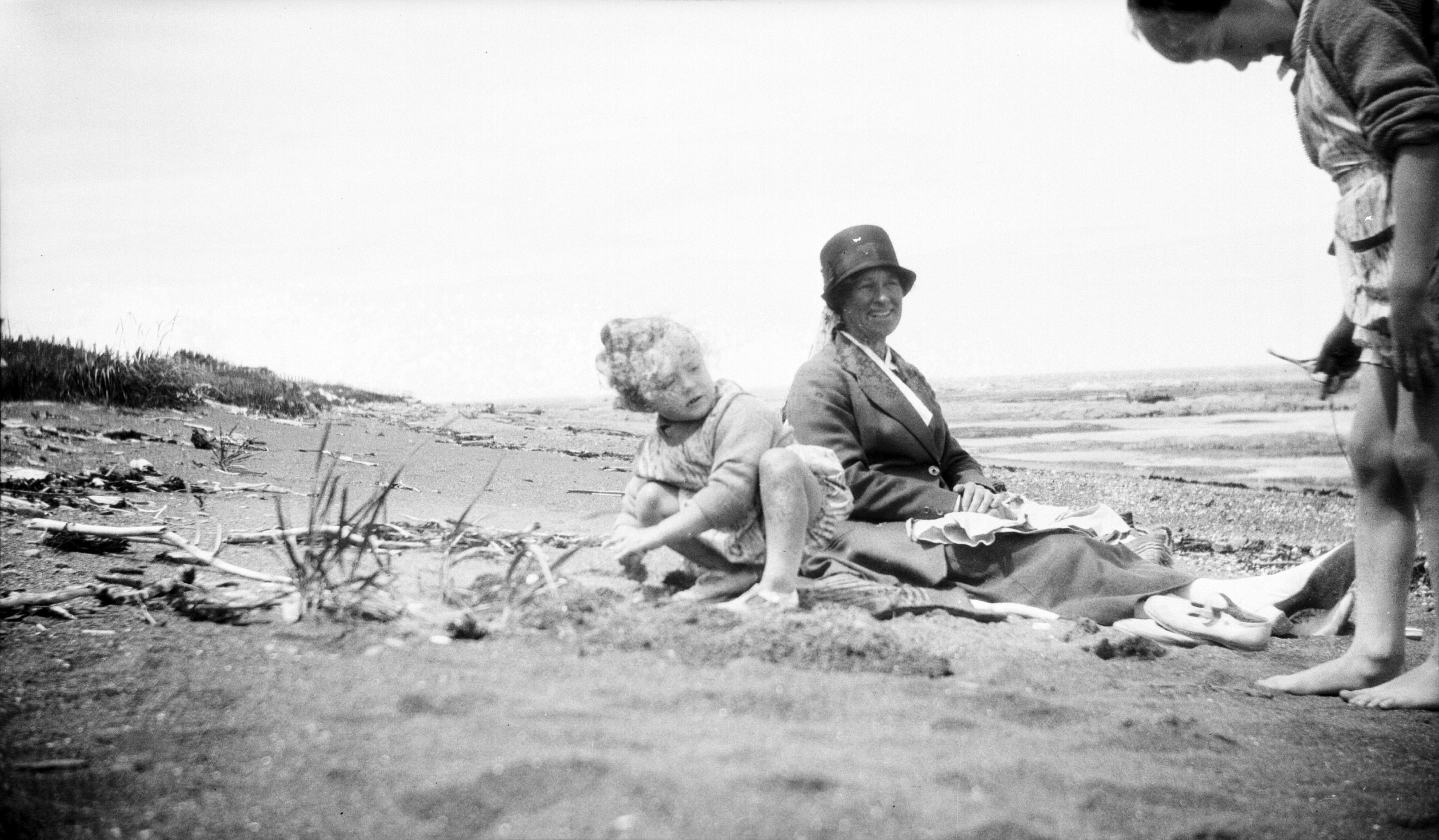 Deux enfants jouent sur la plage à marée basse, surveillés par une femme assise.