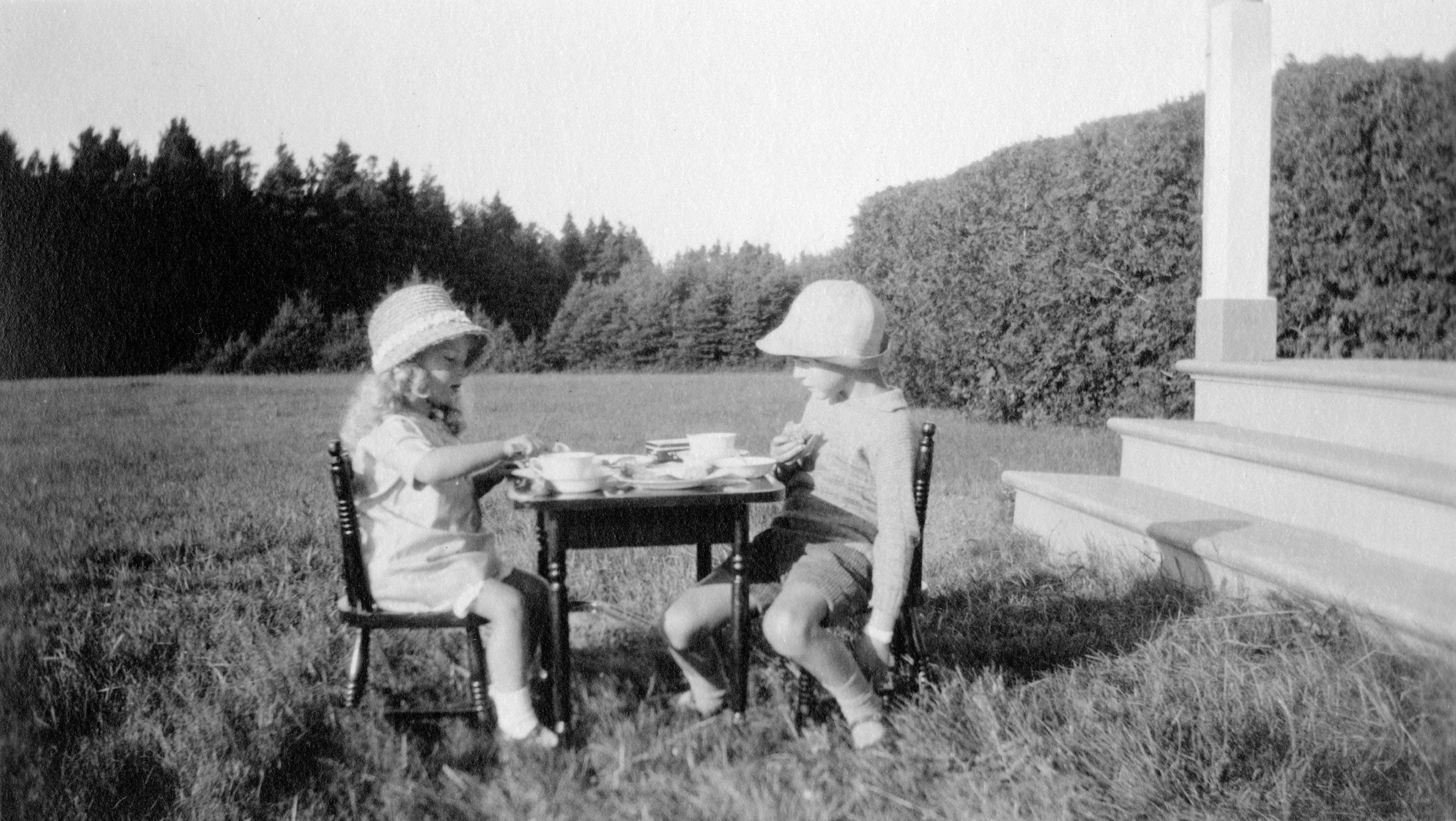 Deux enfants dégustent une collation posée sur une petite table installée à l'extérieur, sur la pelouse.