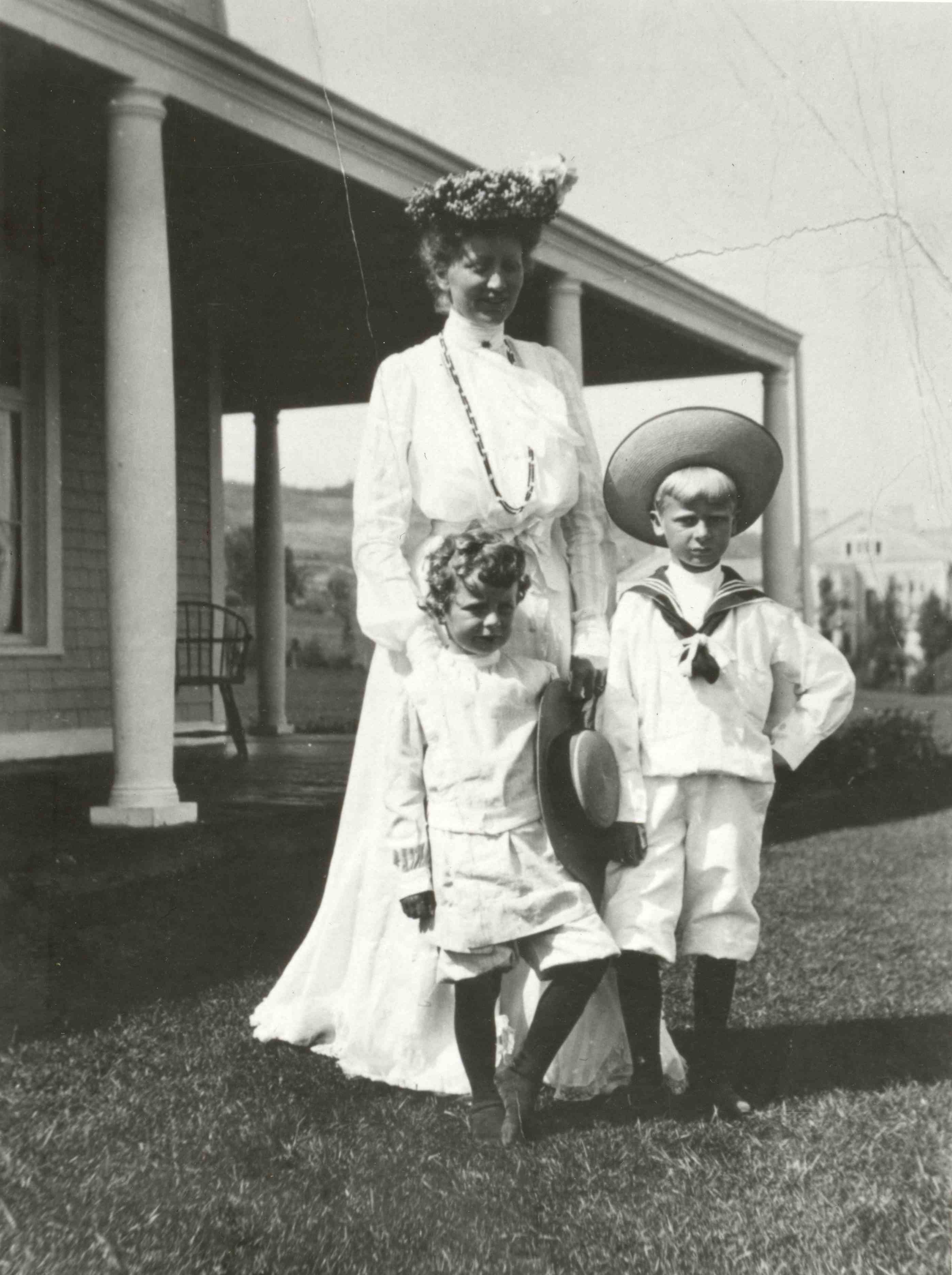 A woman in a very elegant white dress posing with her two children near a house.