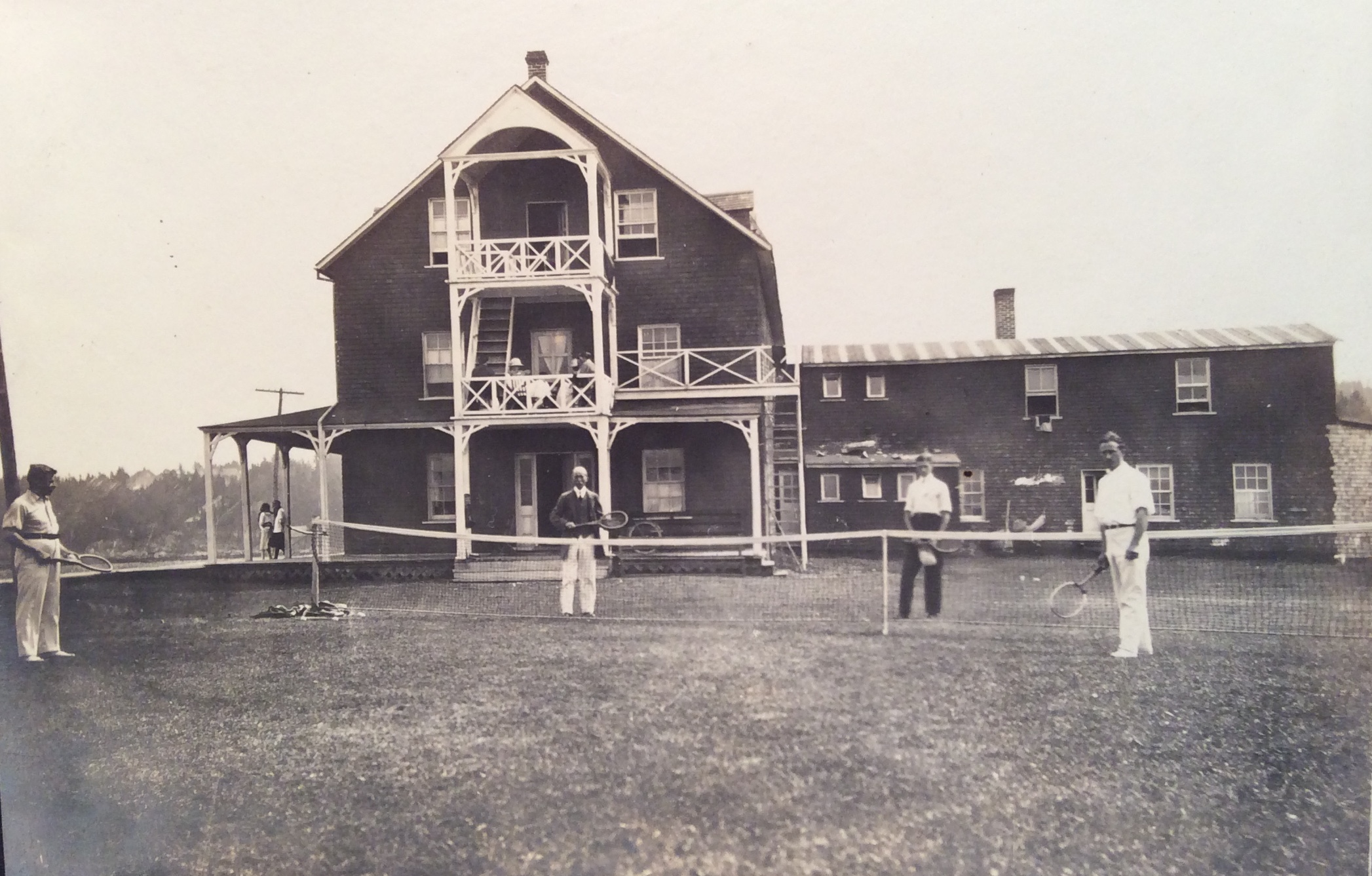 Four men play tennis on the lawn of a hotel on the shore of the St. Lawrence.