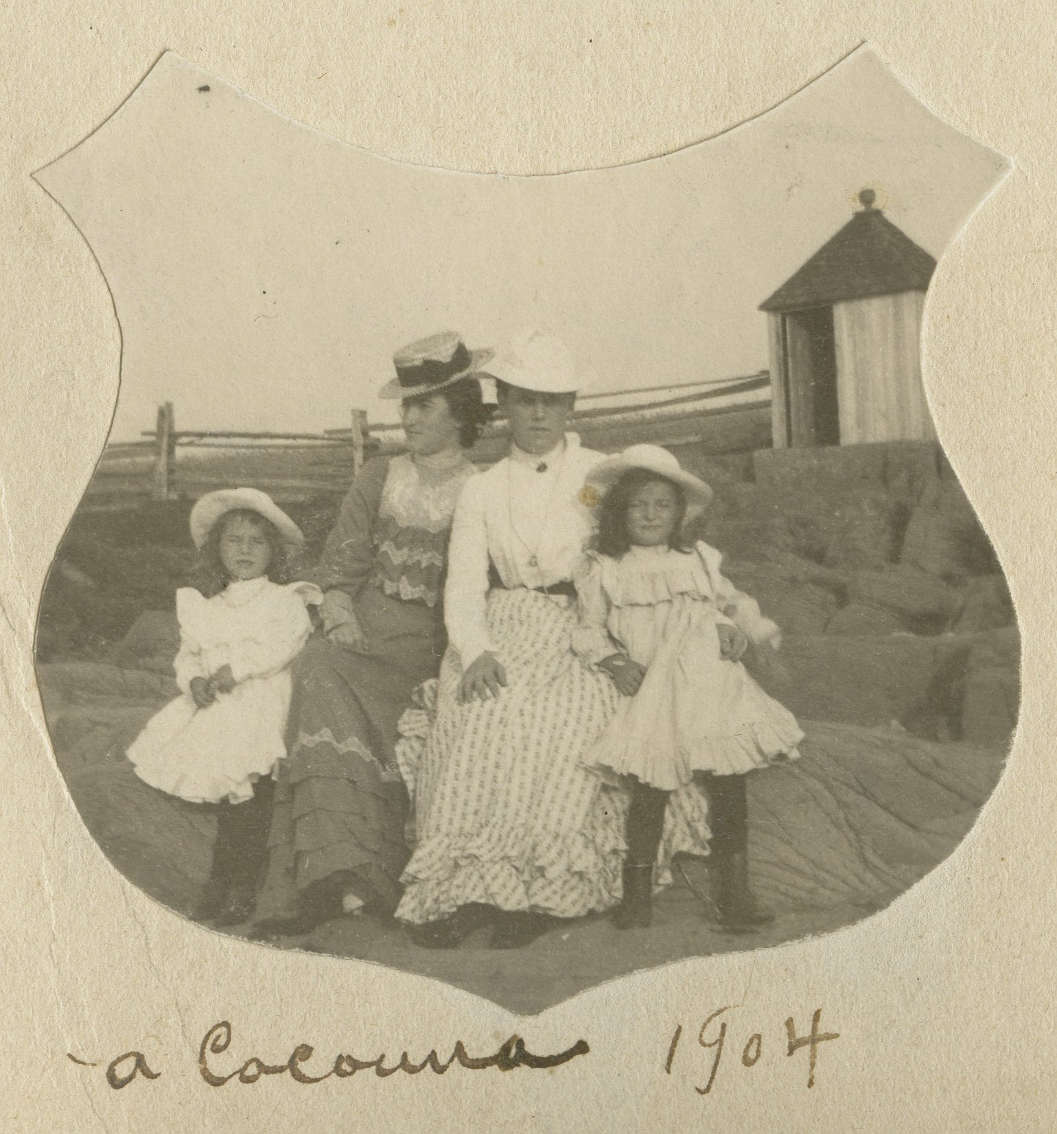 Two young women and two girls pose on rocks by the shore. A changing-cabin is in the background.