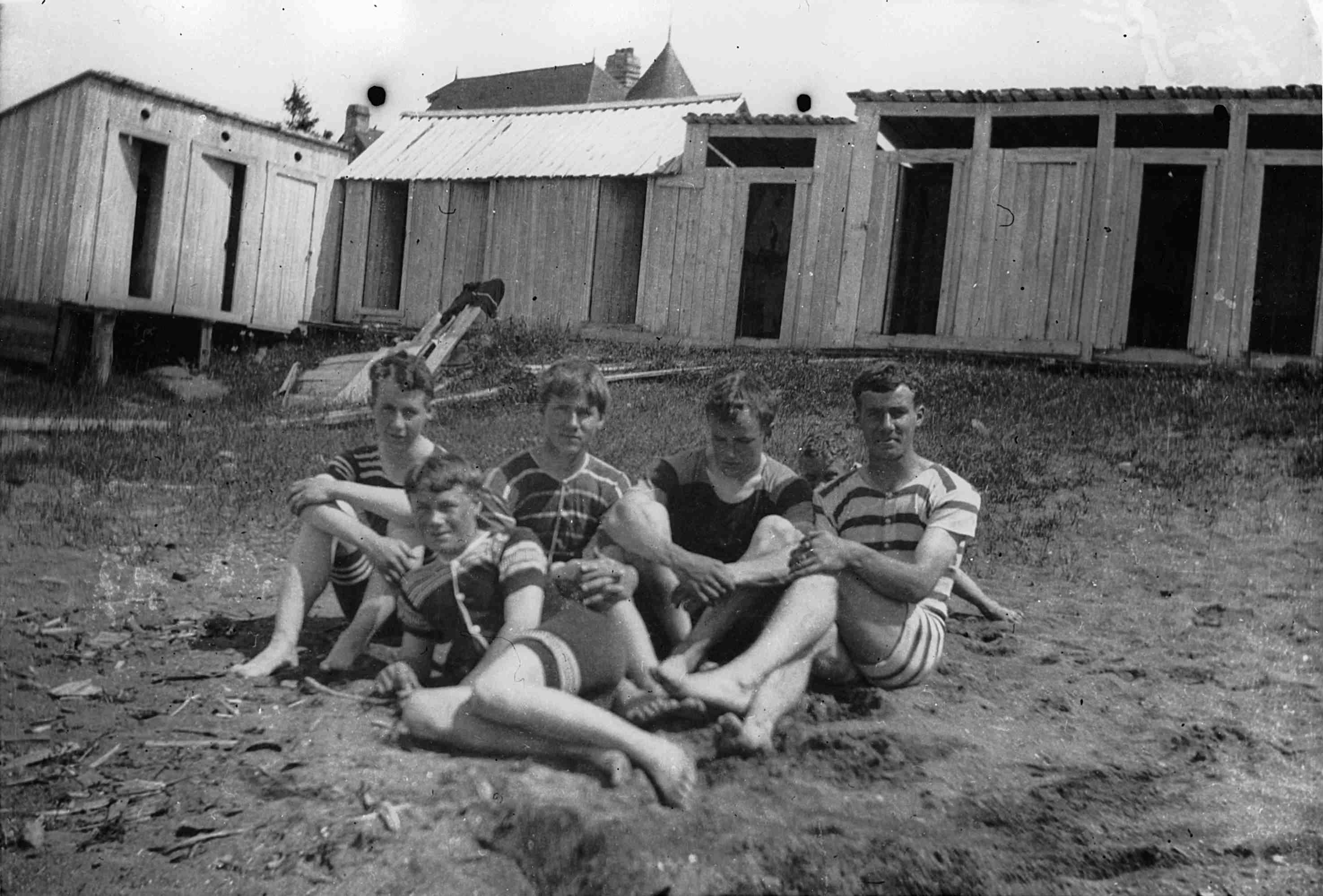 Cinq adolescents vêtus de maillots de bain anciens sont assis dans le sable, près d'une série de cabines.