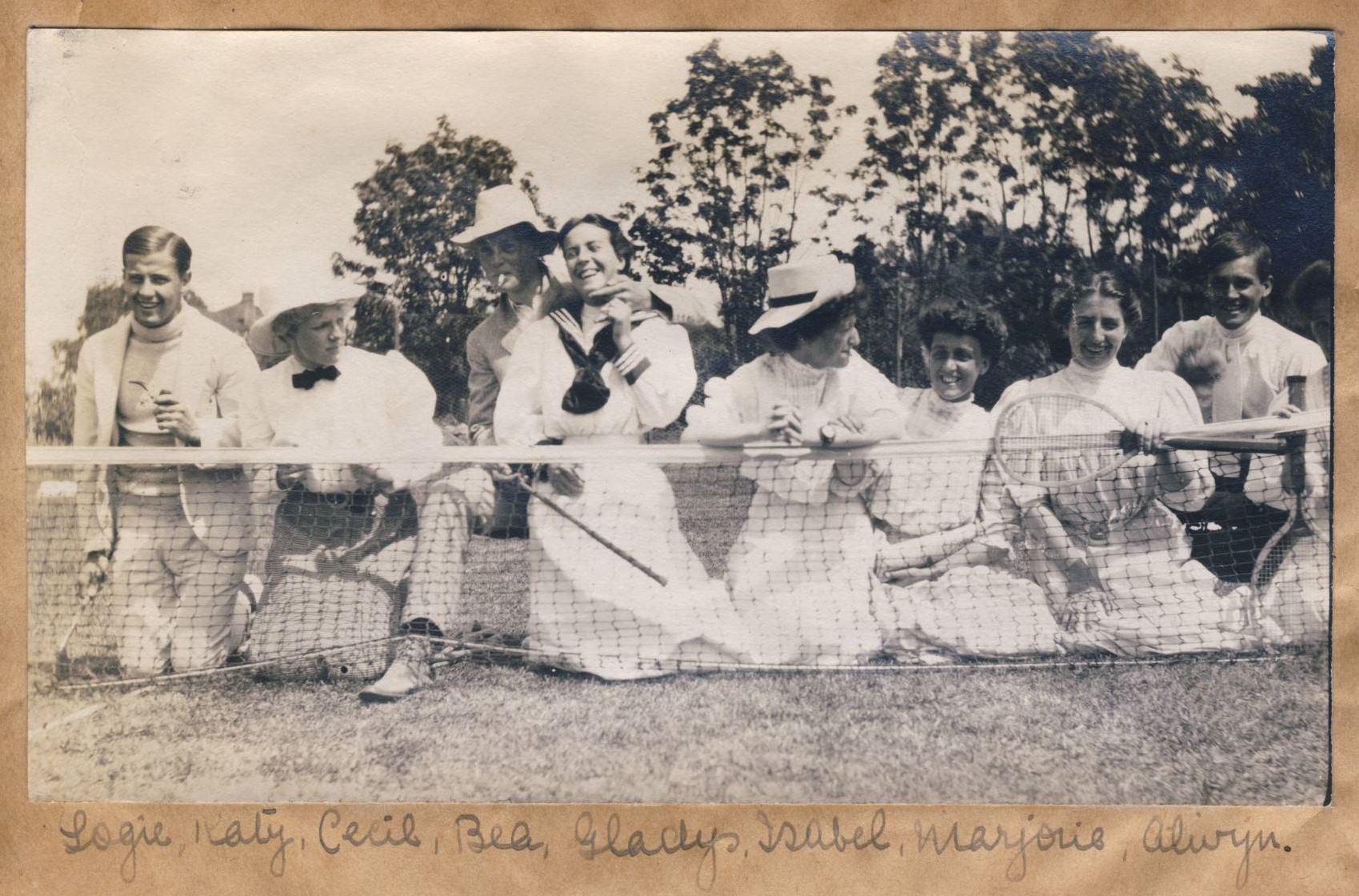 Des joueurs de tennis en robe, en veston ou en chemise sont assis près du filet.