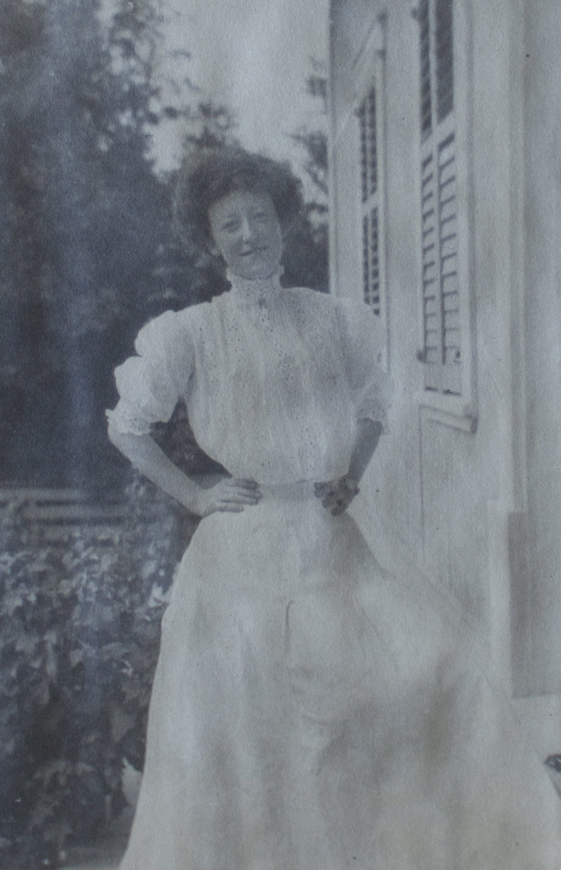 Une femme porte une longue robe blanche dont le col lui couvre tout le cou; elle a la taille extrêmement fine.