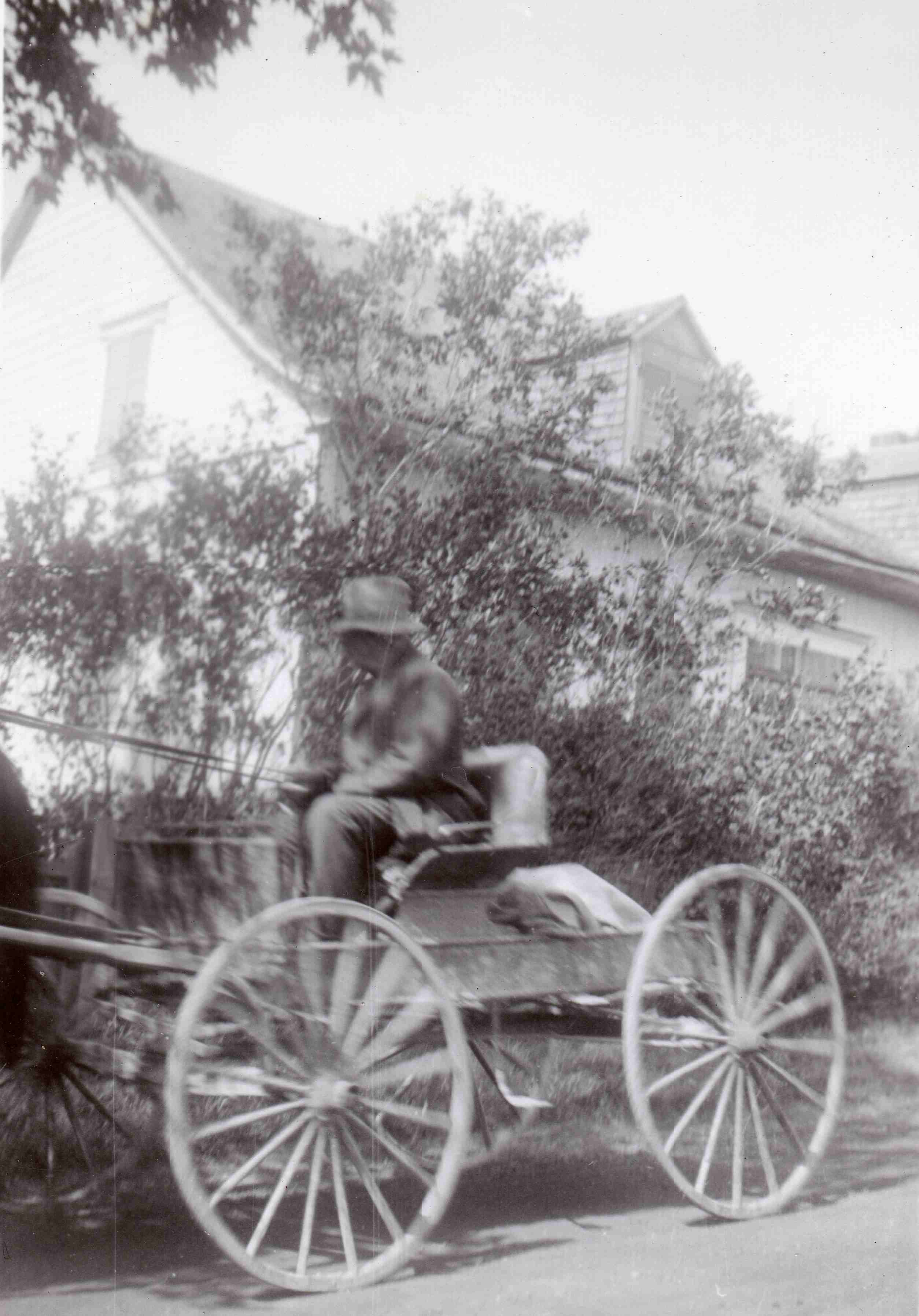 man drives a rustic four-wheeled horse-drawn carriage.
