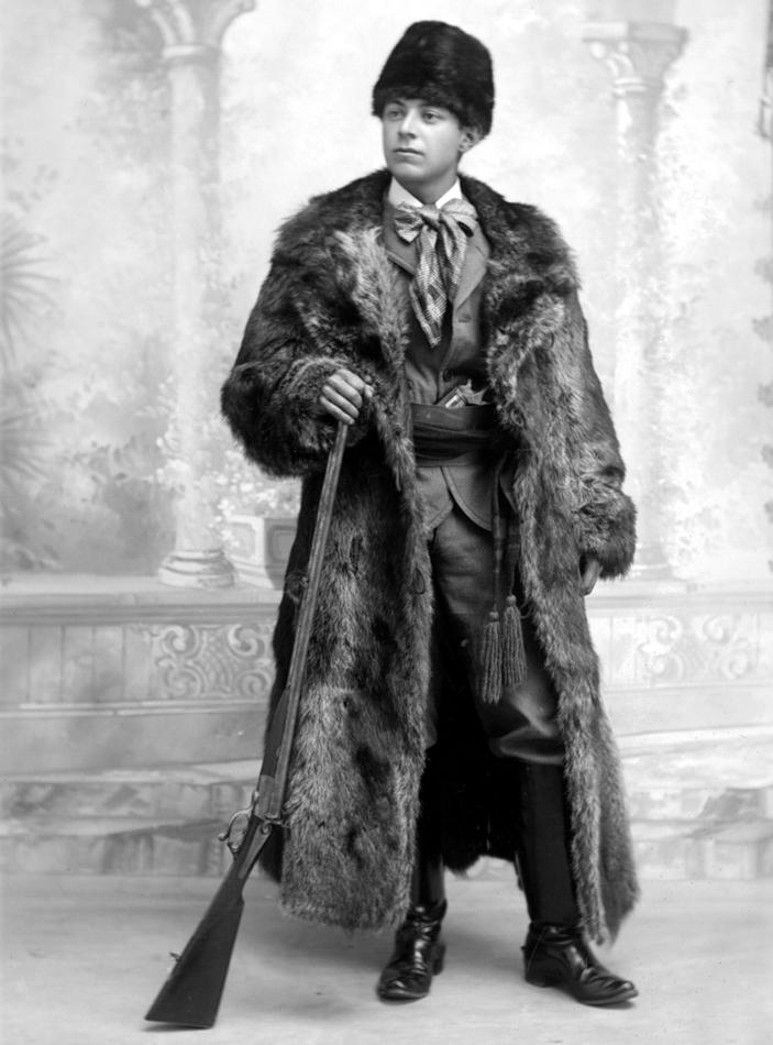 Un jeune homme vêtu d'un manteau et d'un chapeau de fourrure tient un fusil de chasse dans sa main.