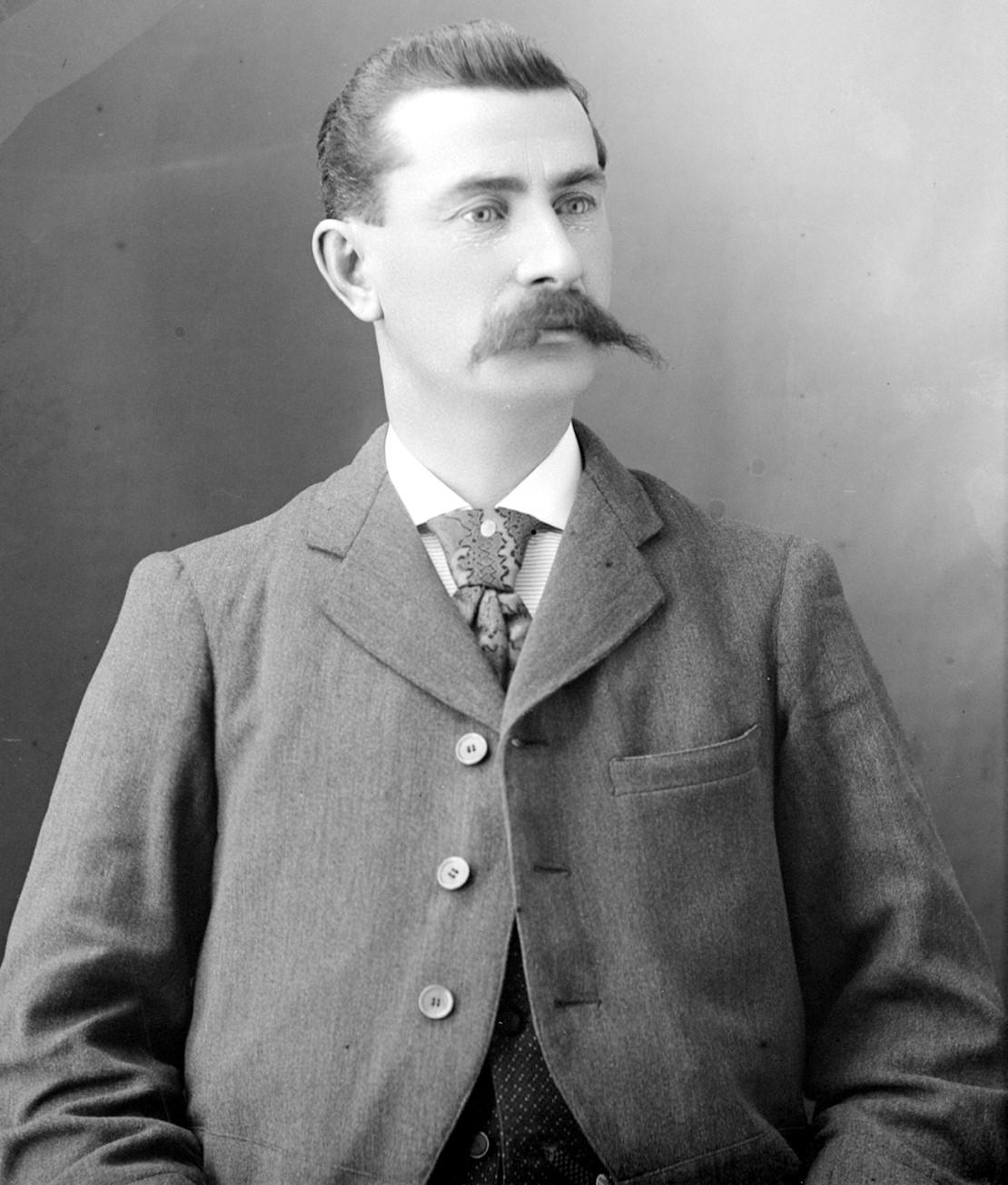Portrait d'un homme distingué portant une moustache proéminente.