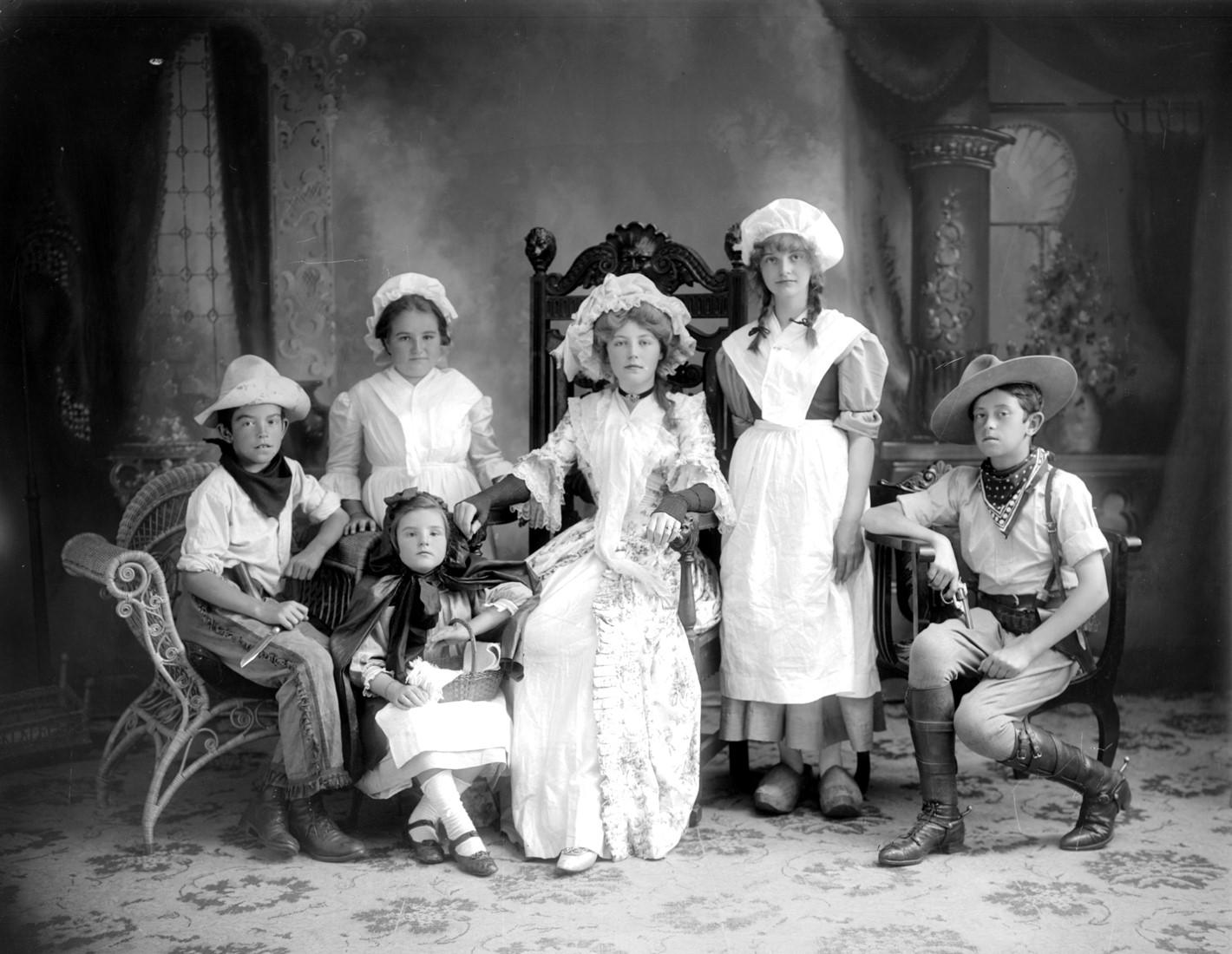 Six enfants déguisés posent fièrement dans un studio de photographie.