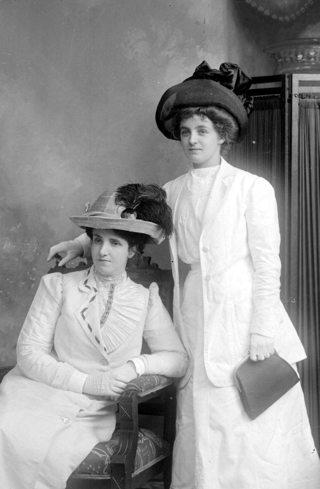 Photographie en noir et blanc de deux élégantes femmes dont les vêtements, les gants y compris, sont blancs ou très pâles.