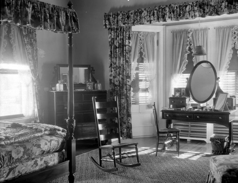 Dans une chambre à coucher se trouvent une coiffeuse et un lit baldaquin décoré de tentures fleuries.