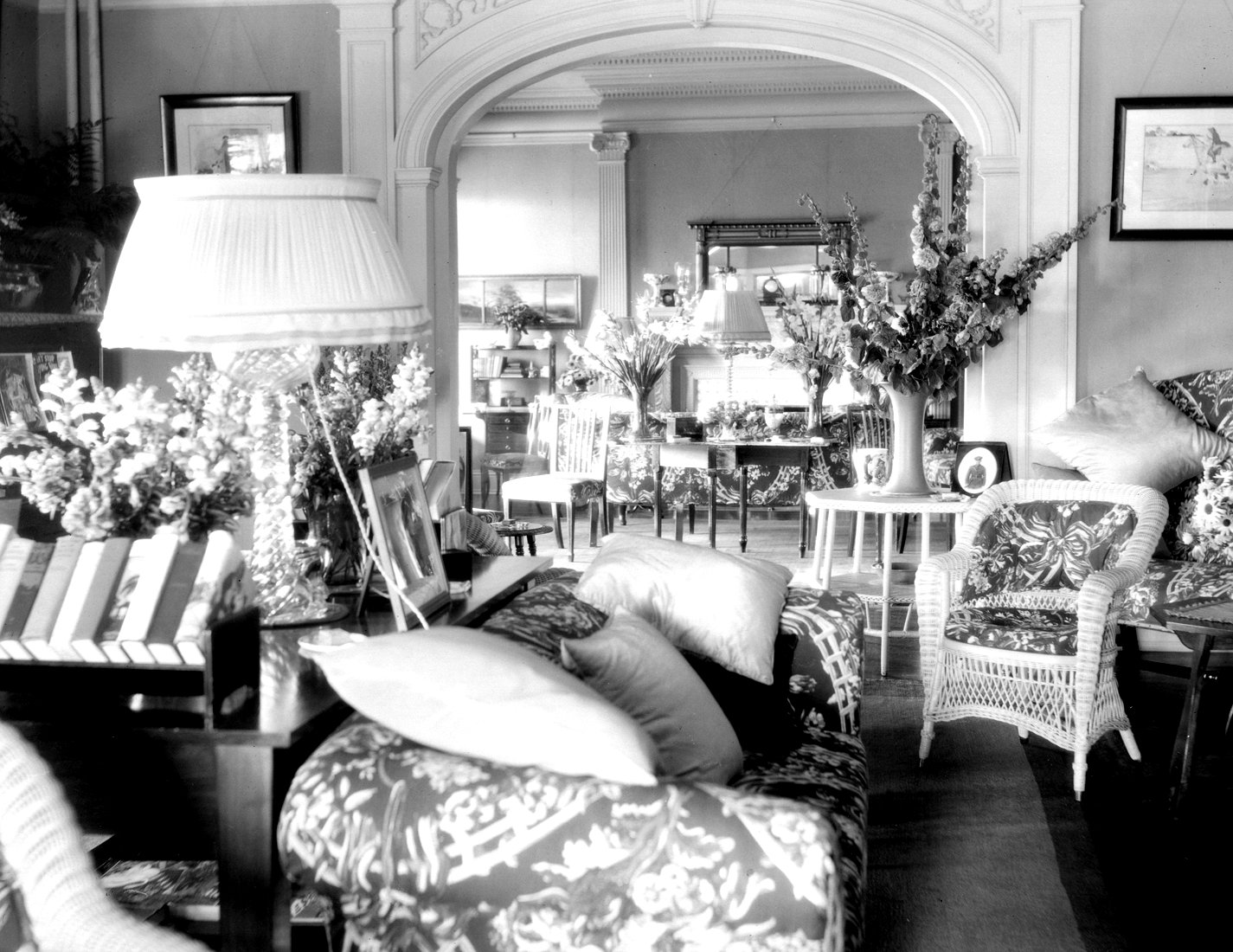 The bright living room of a summer home decorated with bouquets of flowers.