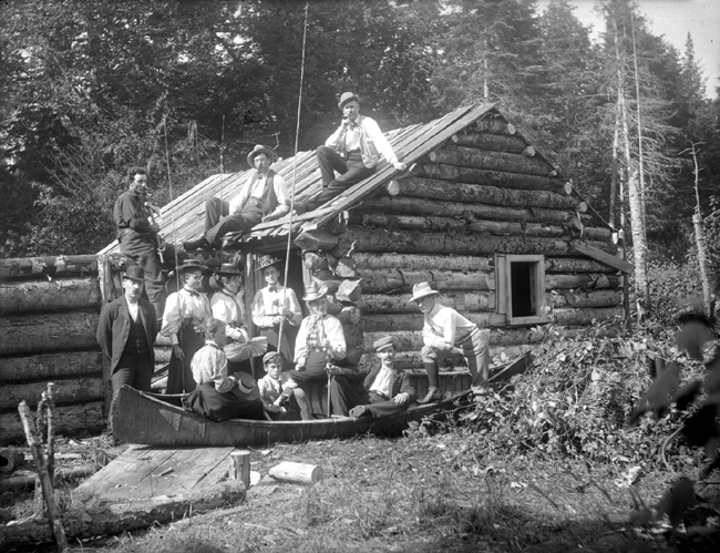 Une famille se tient devant un camp de bois rond.