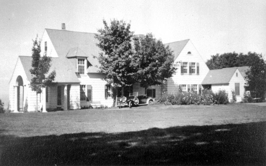 Une villa et son terrain. Une automobile ancienne est stationnée devant la maison.