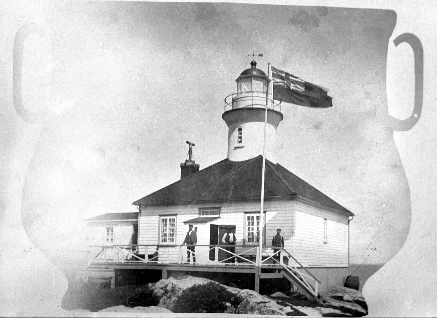 Three men pose in front of a lighthouse on the rocks. The picture is in the shape of an urn with two handles.