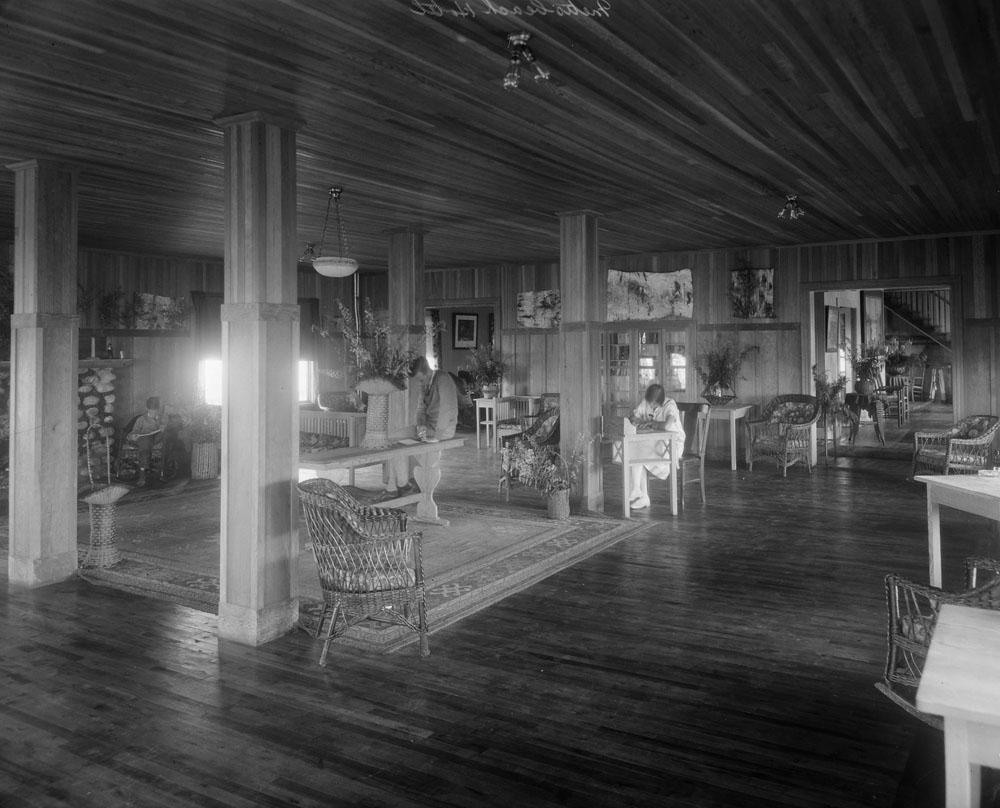 Trois adultes lisent ou écrivent dans la grande salle de séjour l'hôtel Boule Rock aux murs de planches non peintes.