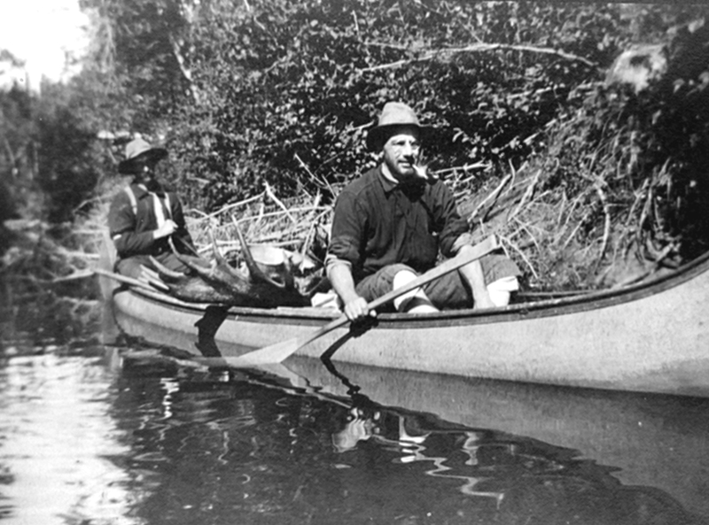 Deux hommes dans un canot transportent un orignal.