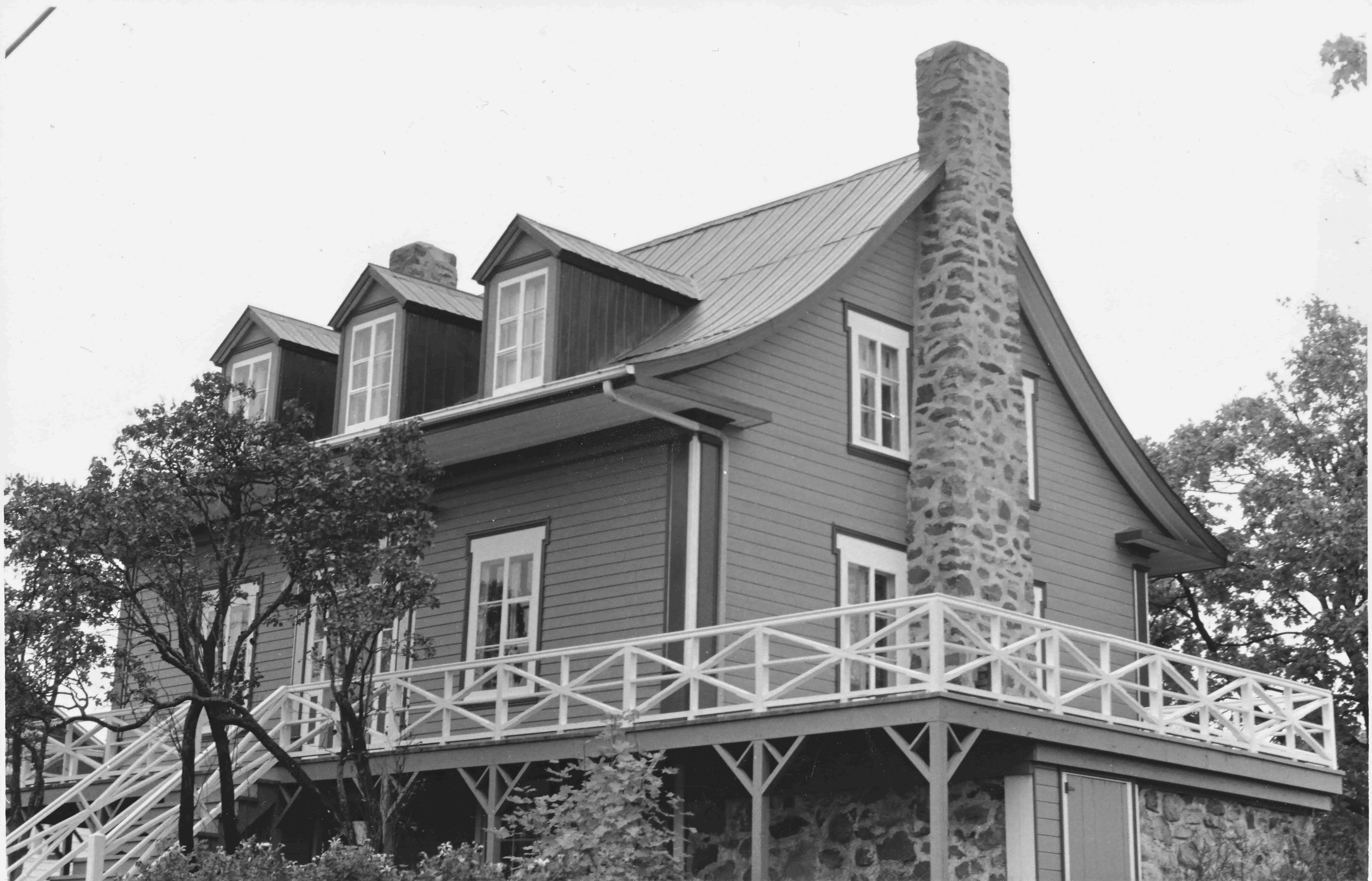 Solide maison québécoise ancienne, avec cheminée de pierre, toit en tôle et murs de planches horizontales en bois.