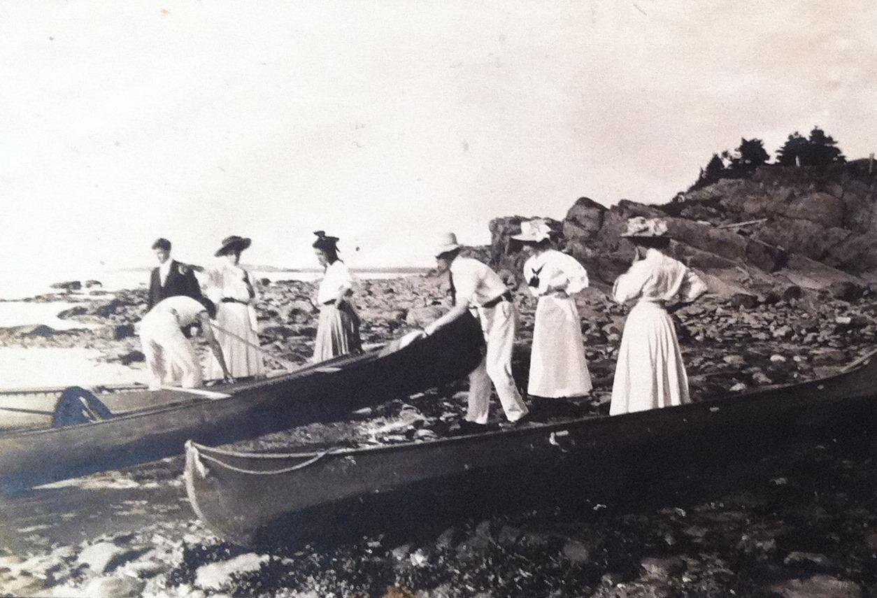 Un petit groupe de personnes s'apprêtant à partir en balade en canot. Presque toutes sont vêtues de blanc ou de couleurs pâles.