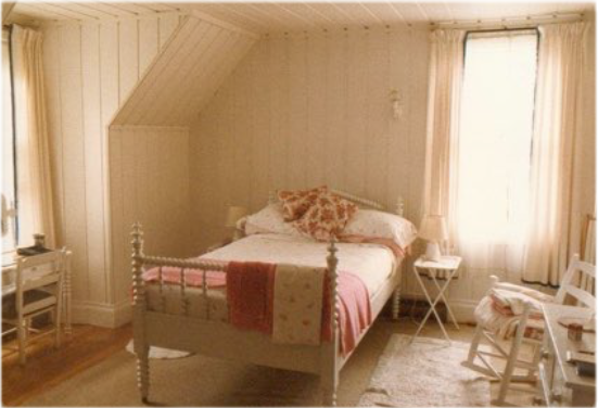 A bedroom with a single bed with a turned-wood bedstead and a dresser, rocker and small desk.