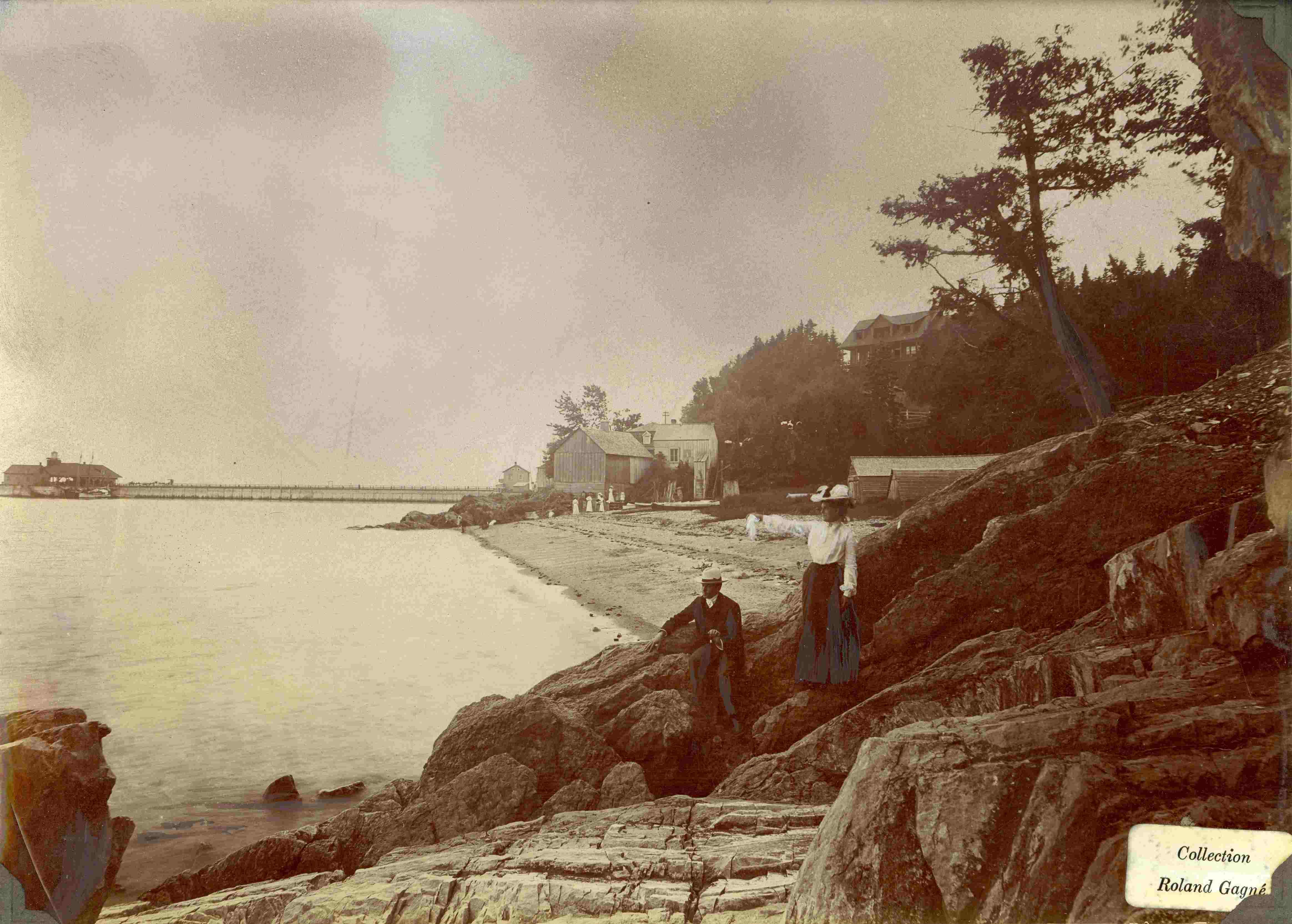 Au premier plan, deux estivants se tiennent sur un grand rocher ; en arrière-plan, une plage et un grand quai.