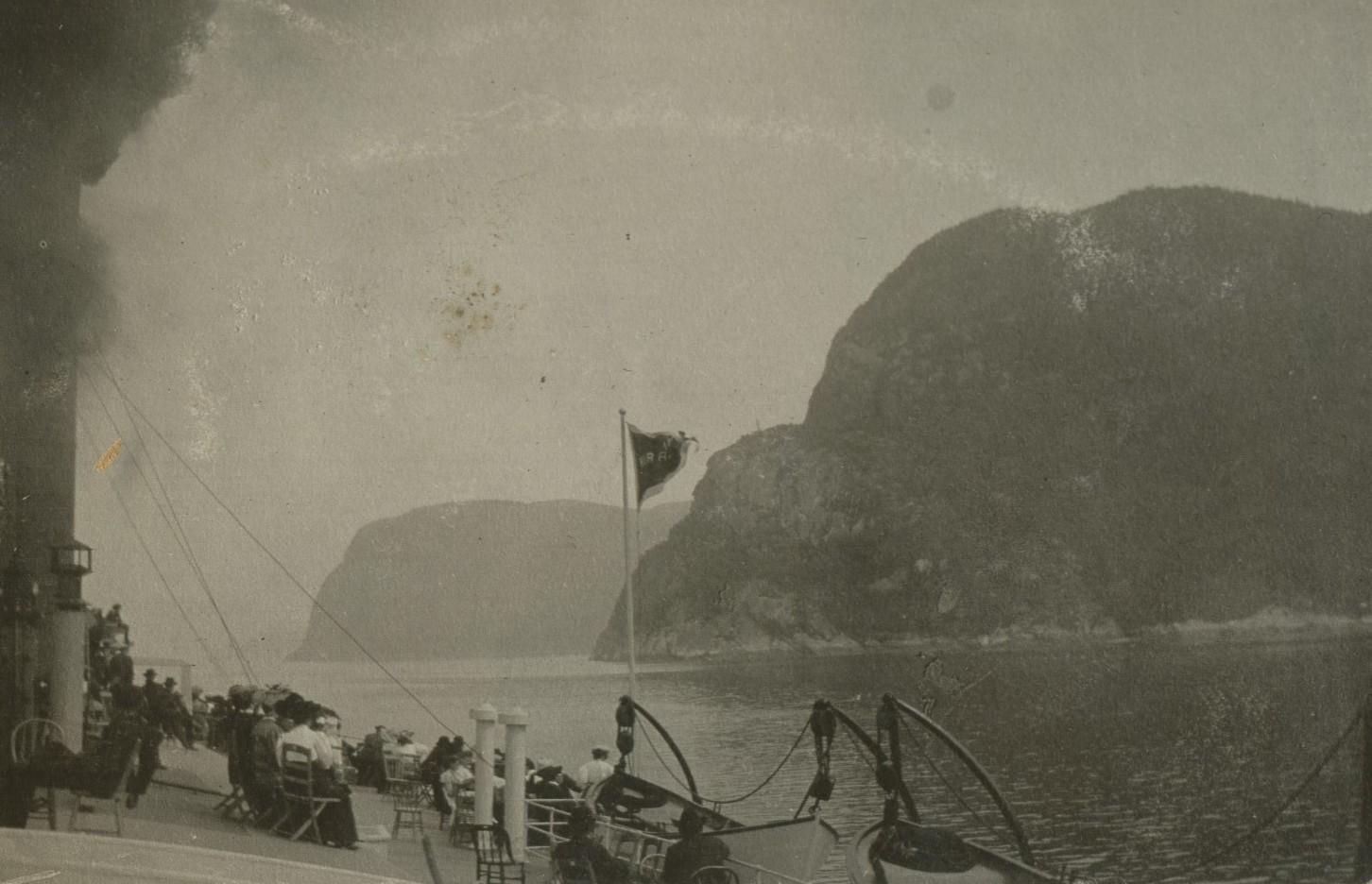 Des passagers sont assis sur le pont d'un navire à vapeur. Ils observent les rochers abrupts sur la rive.