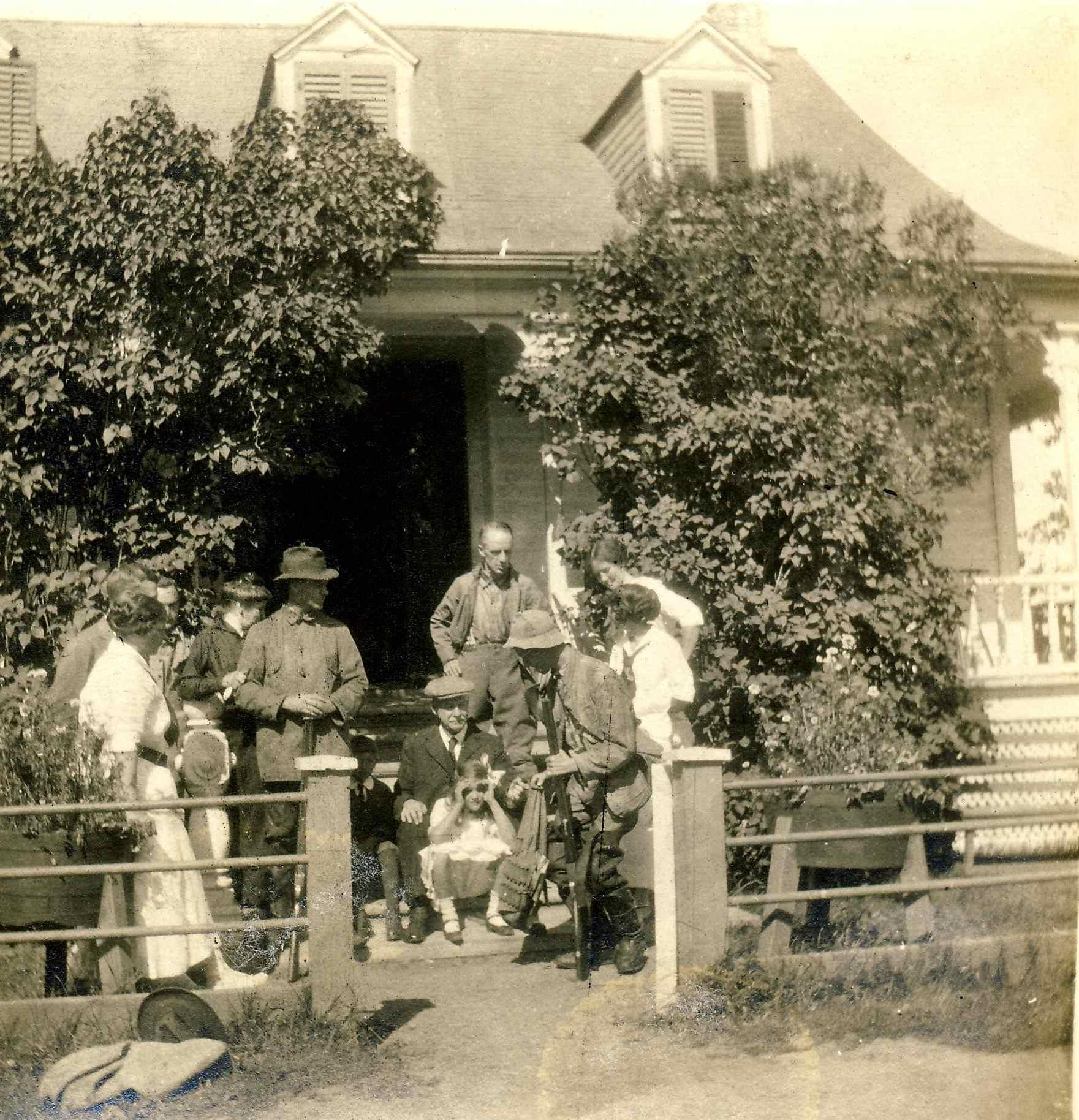 Deux chasseurs sont entourés de quelques personnes devant une maison rurale bordée de lilas.