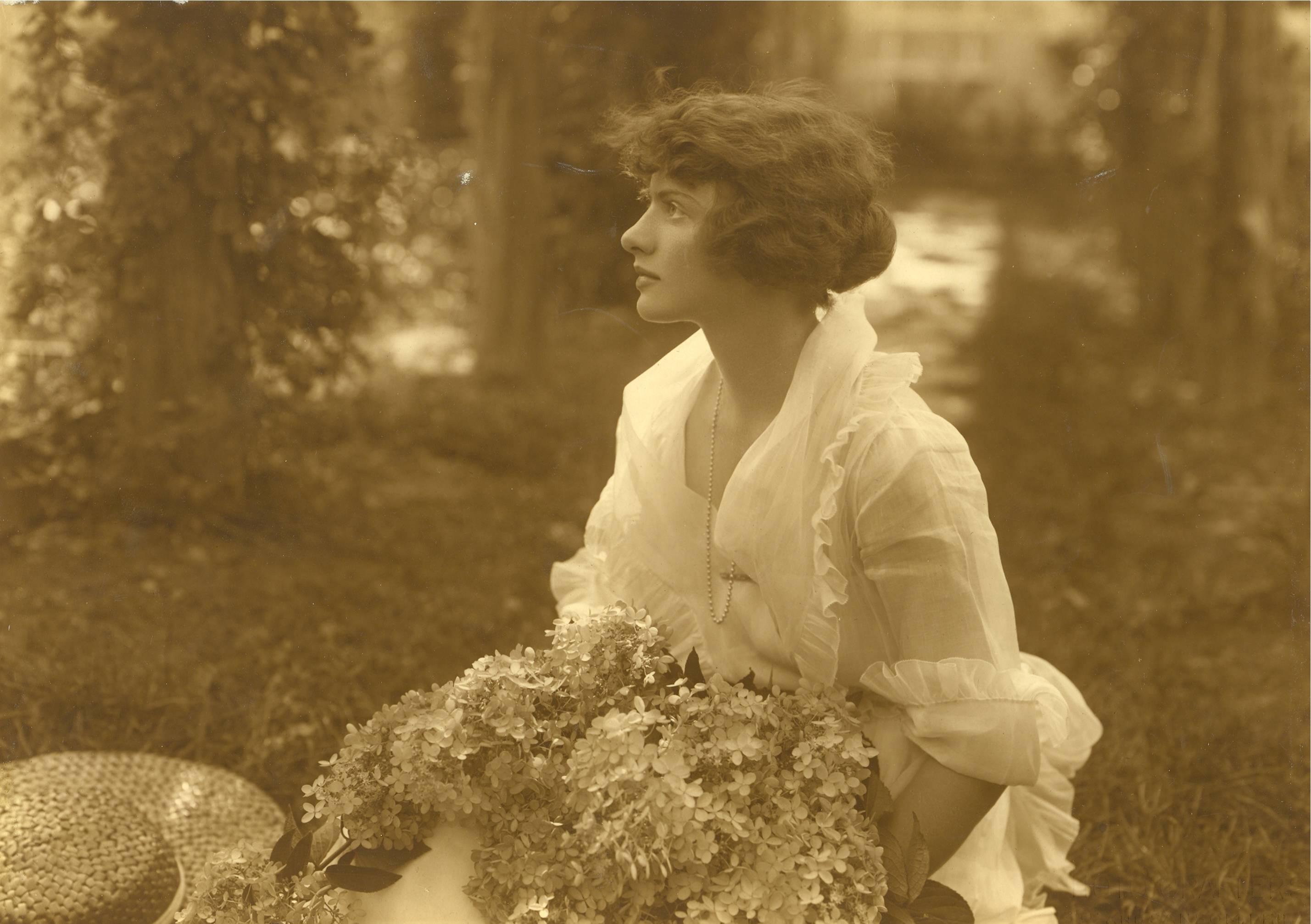 Une jeune femme de profil tient un imposant bouquet de fleurs. Elle porte une blouse blanche légère.
