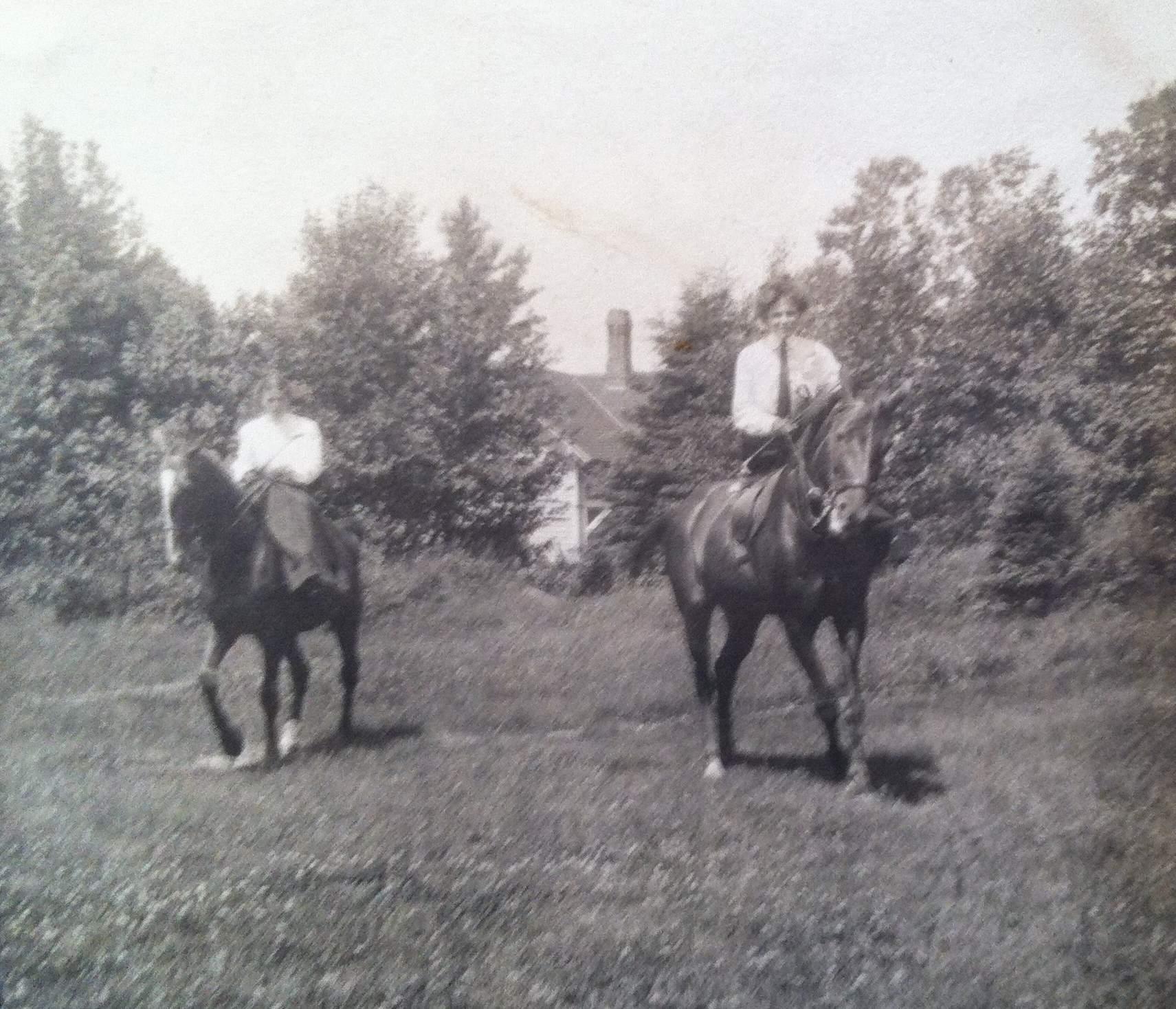 Deux cavalières montent à cheval, sur un terrain bordé d'arbres.