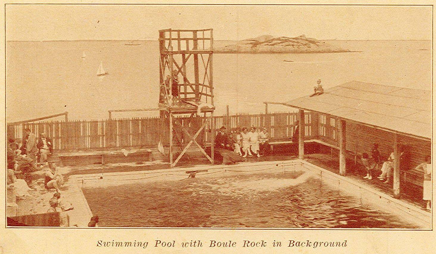 Plusieurs personnes se trouvent autour d'une piscine clôturée, avec un grand plongeoir.