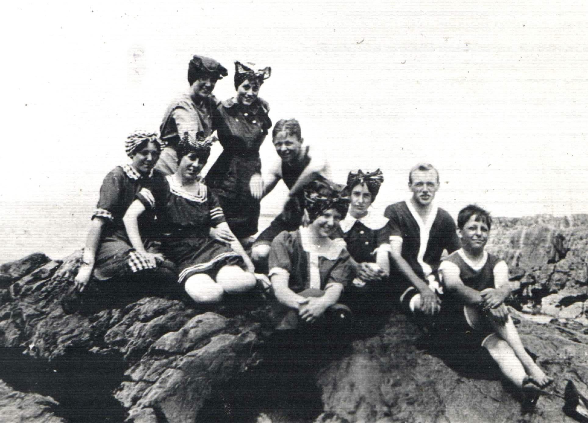 Neuf jeunes personnes posent sur un rocher au bord du fleuve, vêtus de maillots de bains du début du vingtième siècle.