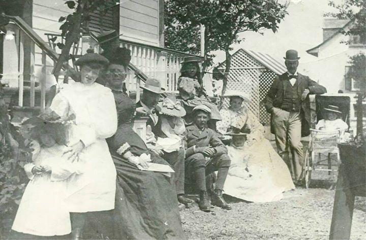 Photographie noir et blanc présentant une famille d'une dizaine de personnes bien vêtues devant une maison.