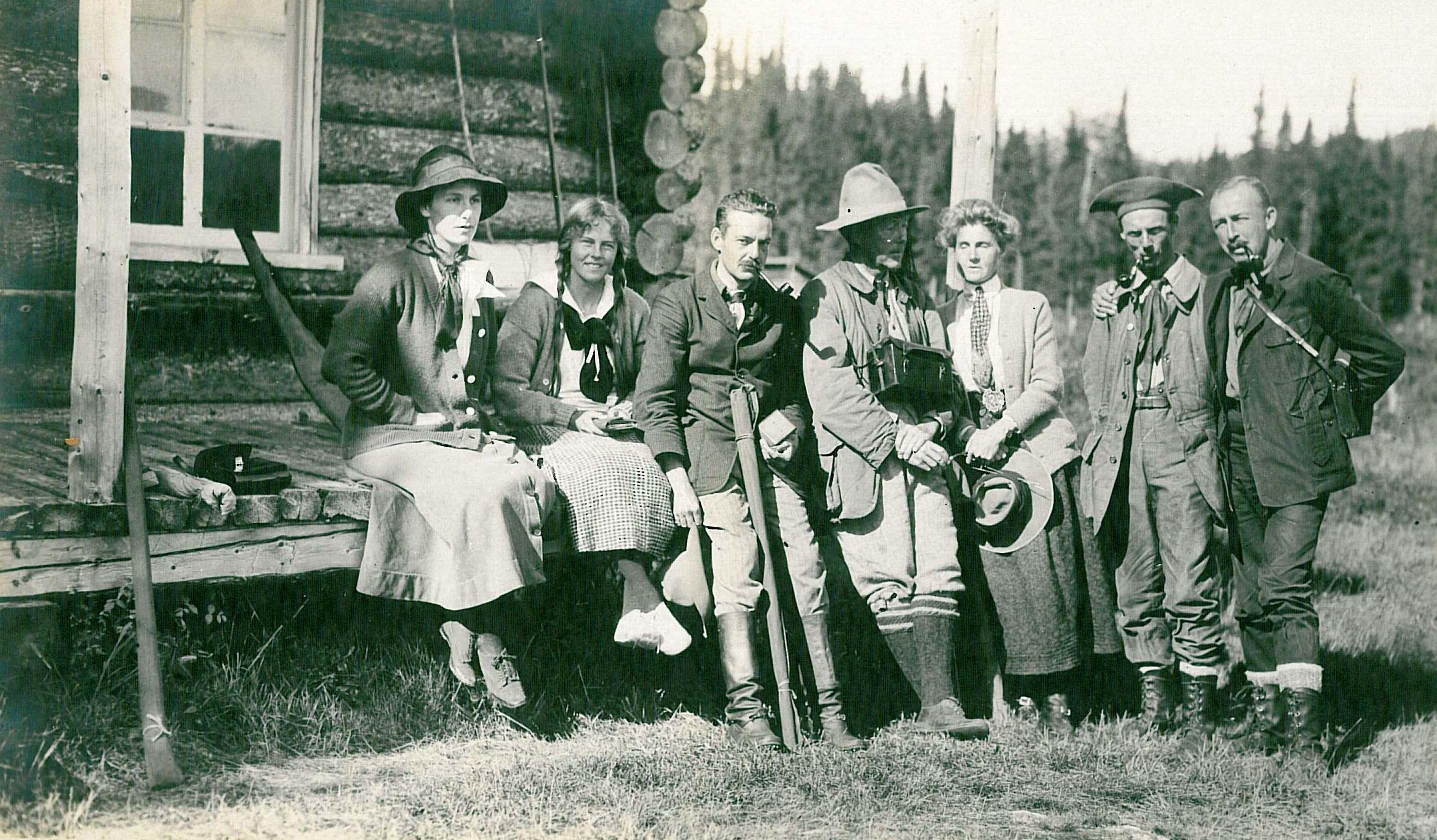 Quatre hommes et trois femmes posent devant un camp de chasse et pêche en rondins.