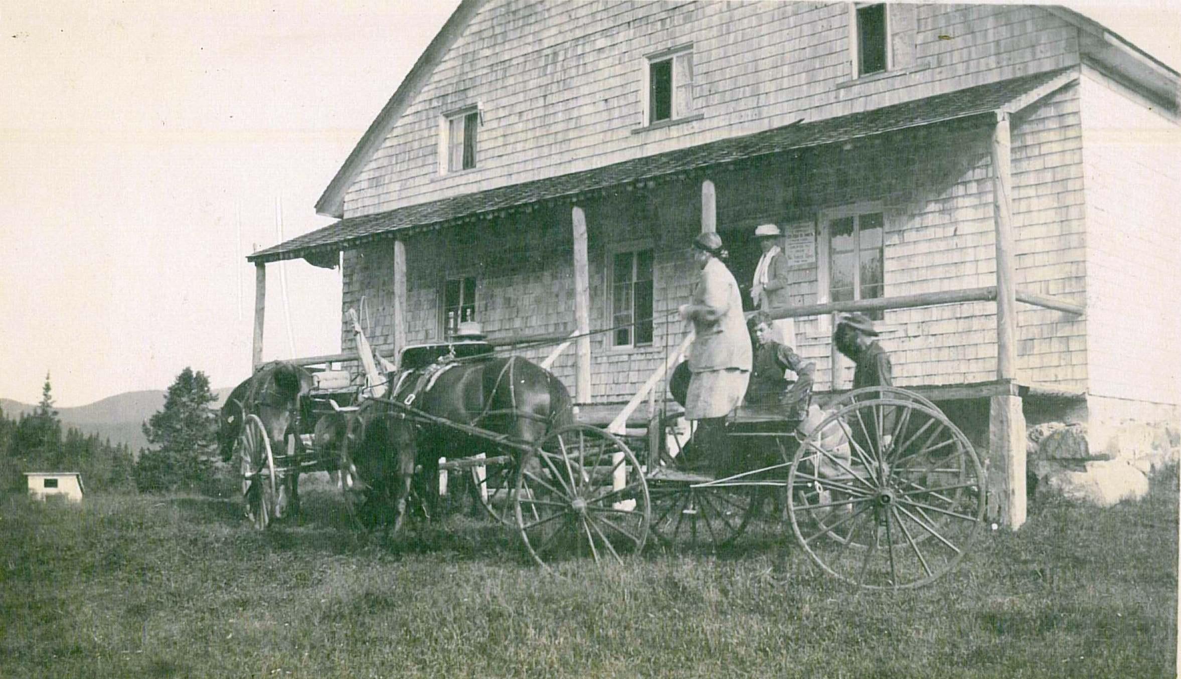 Quatre personnes sont devant un bâtiment en bardeaux de cèdre, où attendent deux chevaux attelés à des voitures à quatre roues.