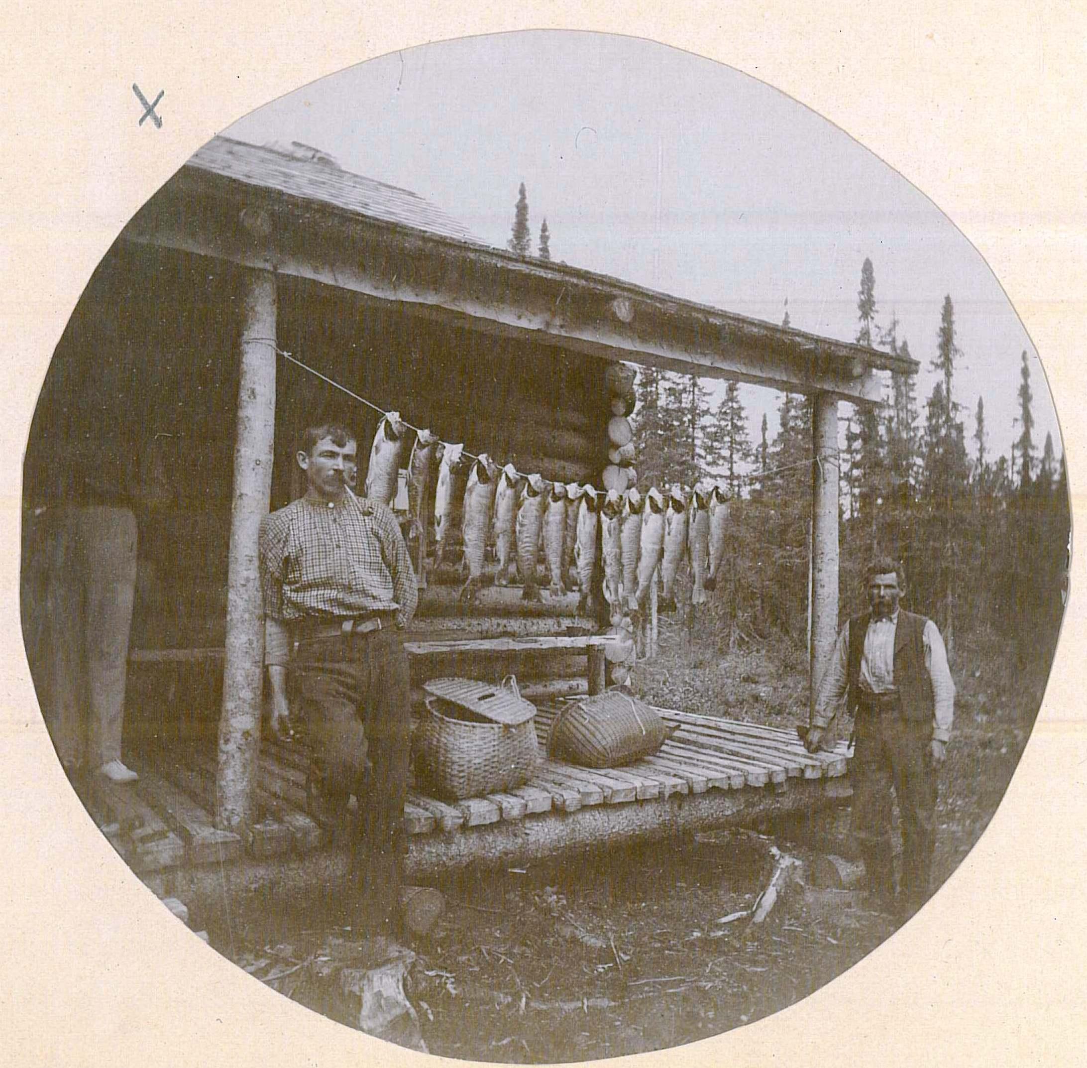 Deux hommes posent près d'un peu plus d'une douzaine de poissons suspendus sous le toit de la galerie d'un camp de pêche.