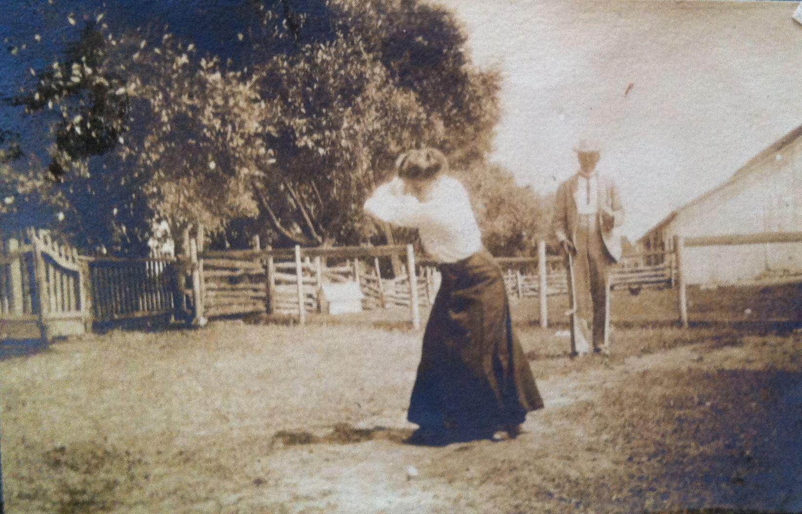 Une femme s'apprête à frapper une balle de golf pendant qu'un homme attend, en retrait.