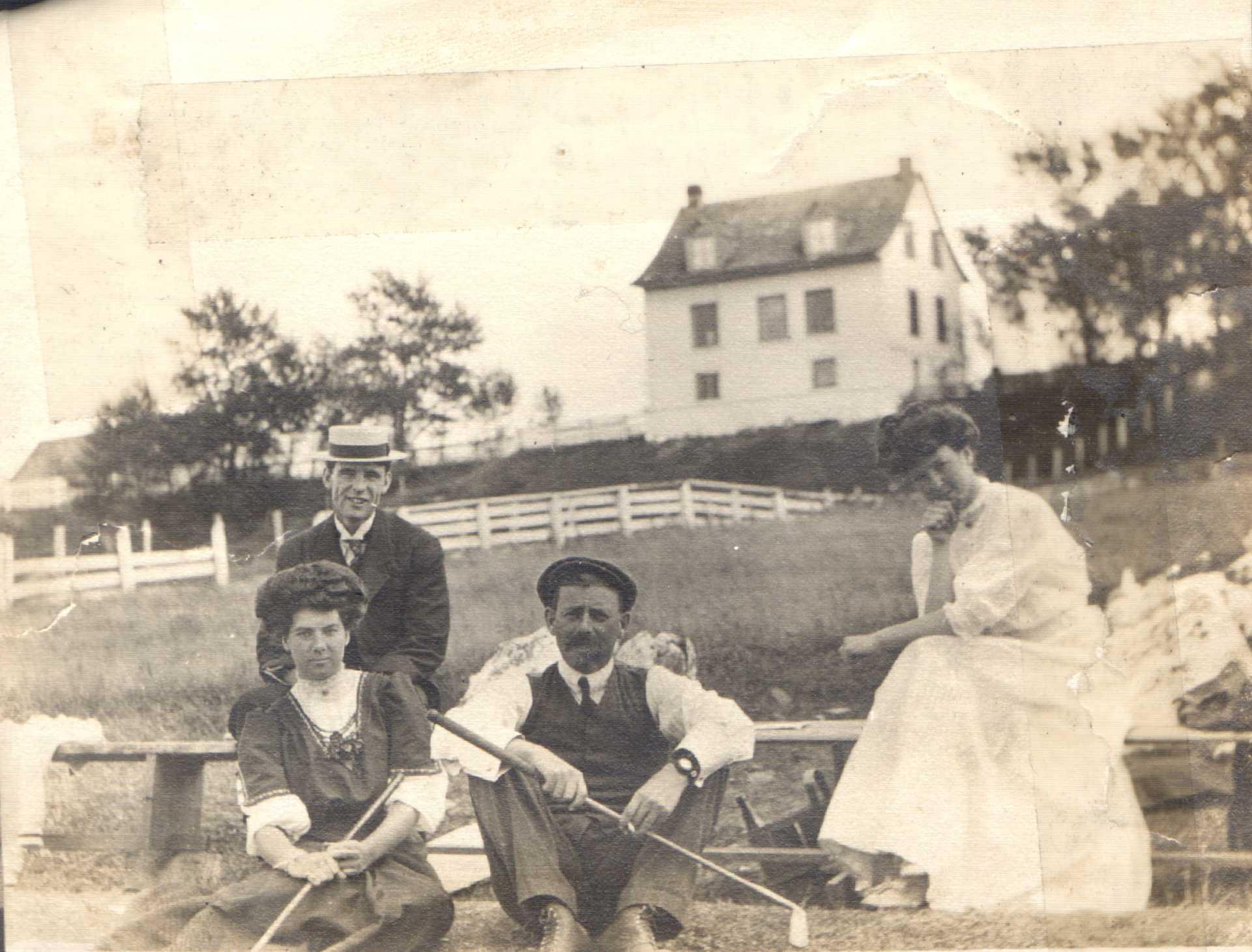 Photographie présentant deux hommes et deux femmes assis ; deux d'entre eux tiennent des bâtons de golf.