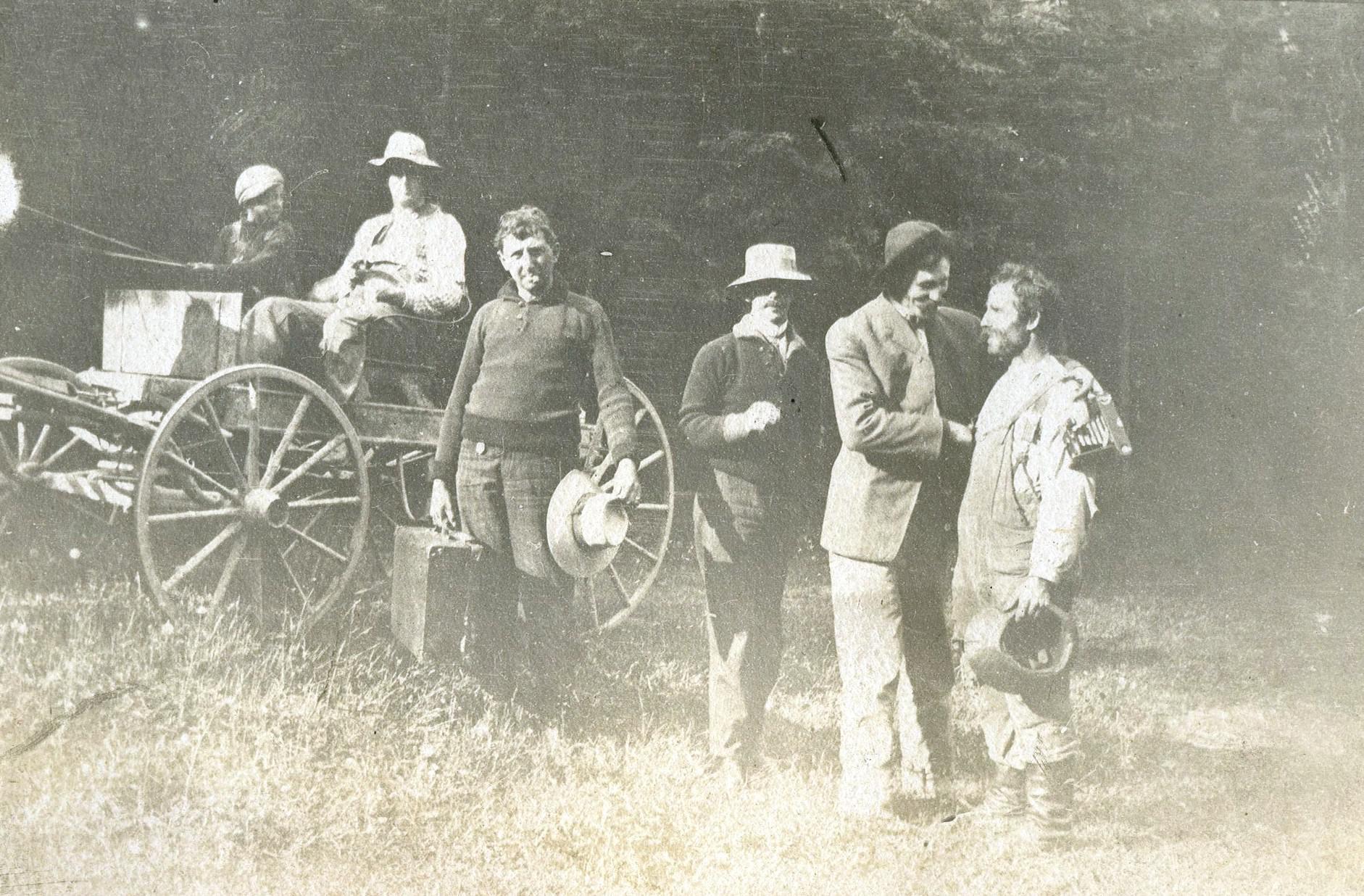 Des hommes se tenant près d'une voiture à cheval rencontrent un homme en vêtements de travail.