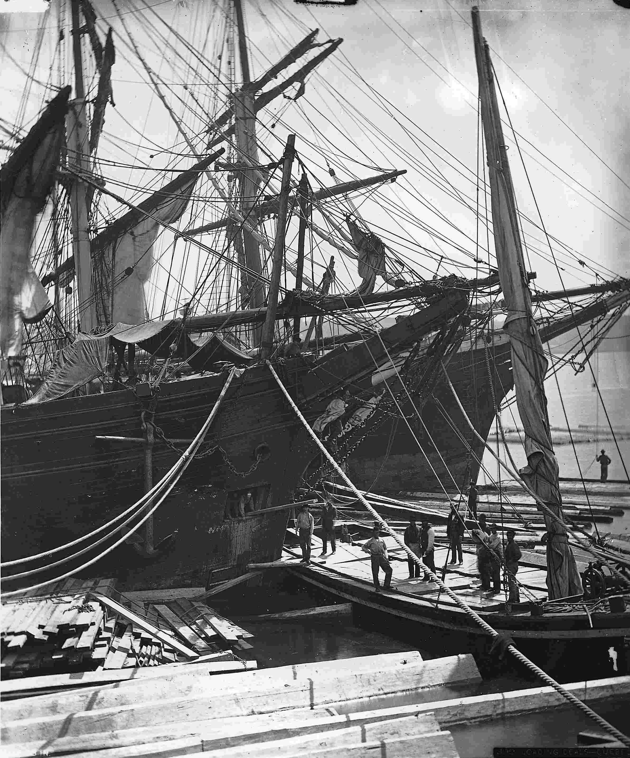 Une dizaine d'hommes participent au déchargement d'un grand bateau à voile servant au transport du bois.