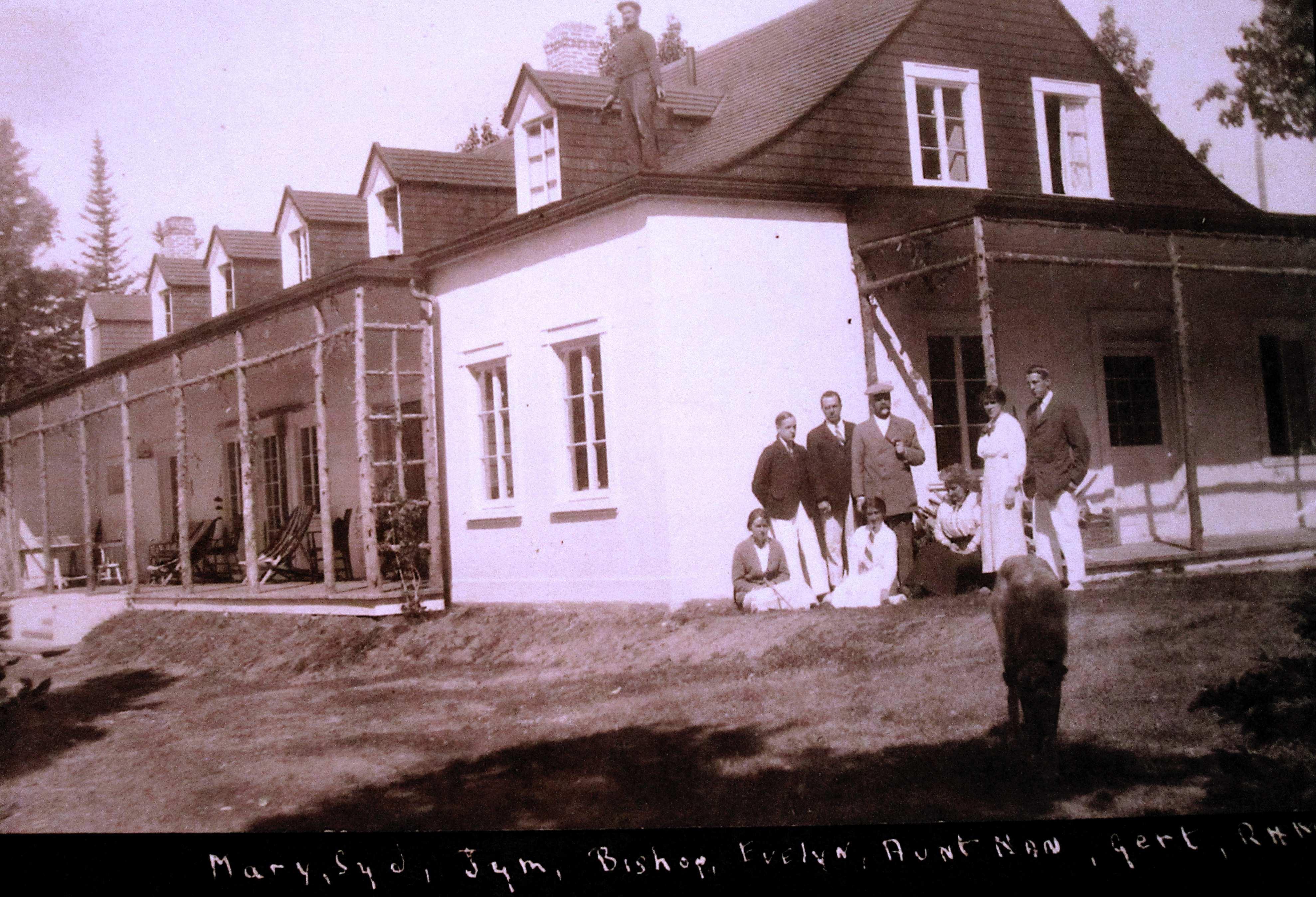 Quelques personnes posent devant une grande résidence d'été ; un ouvrier est debout sur le toit.