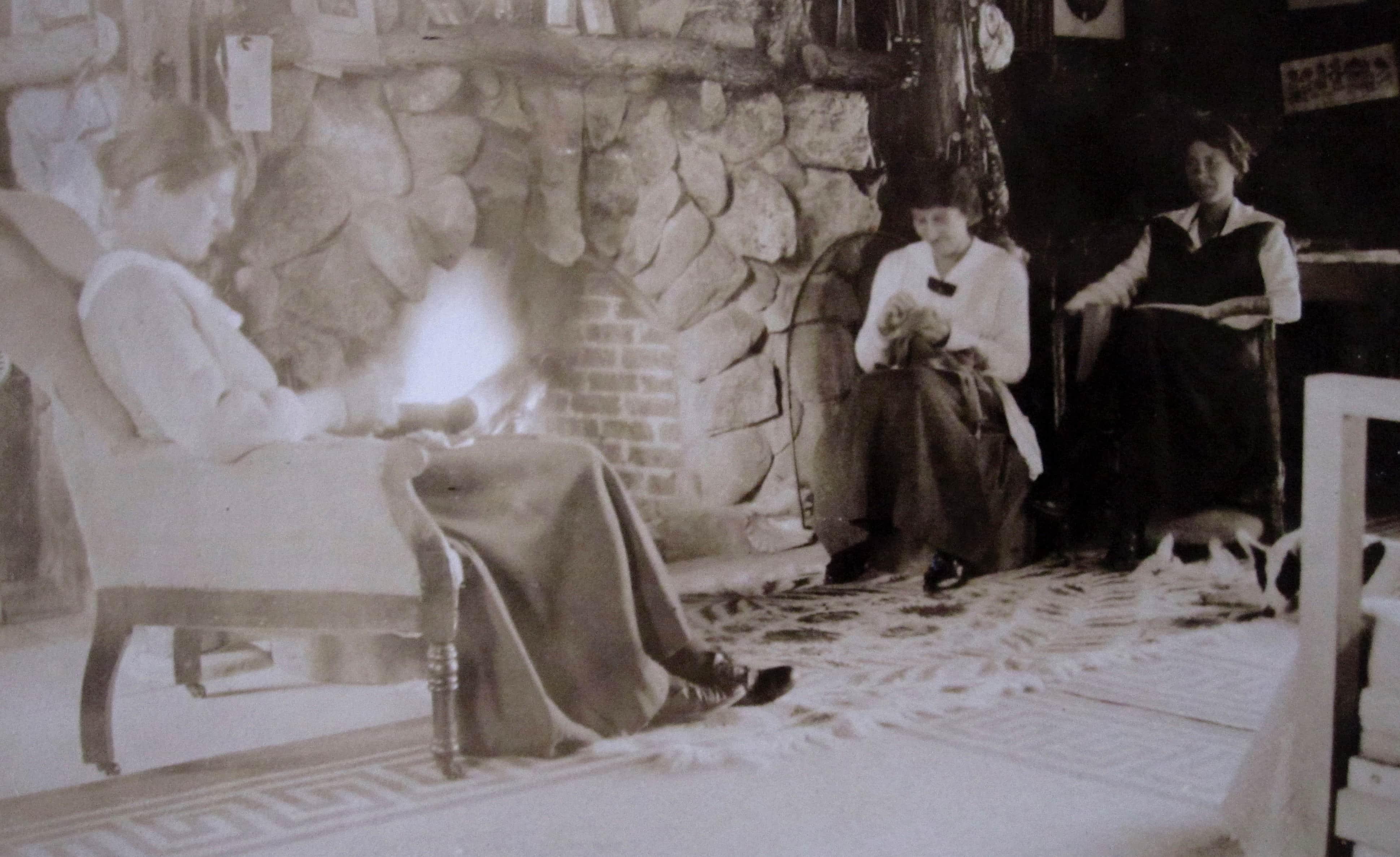 Trois jeunes femmes lisent devant le feu d'un foyer en pierre des champs.