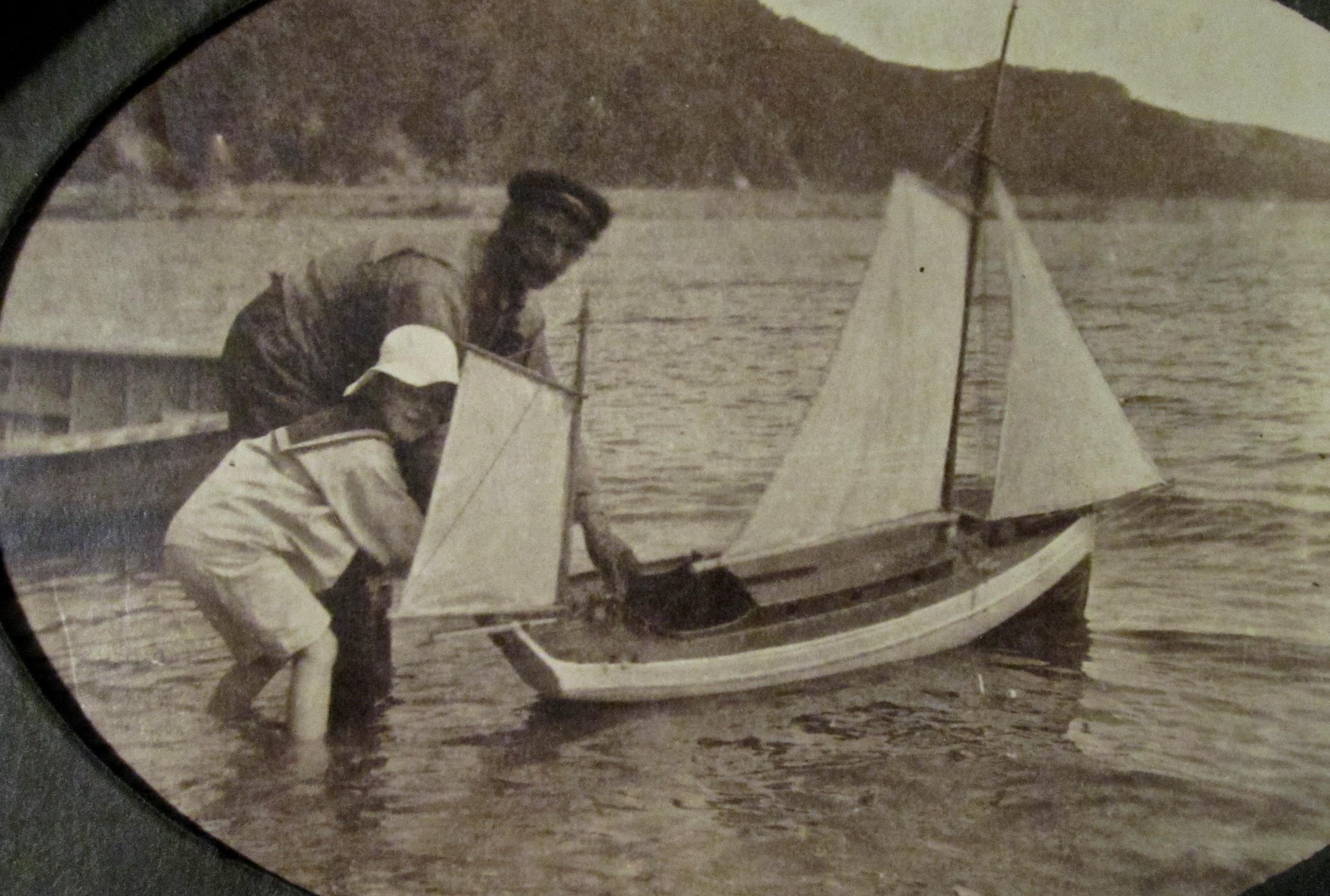 Un adulte aide un enfant habillé en matelot à mettre à l'eau son bateau jouet.