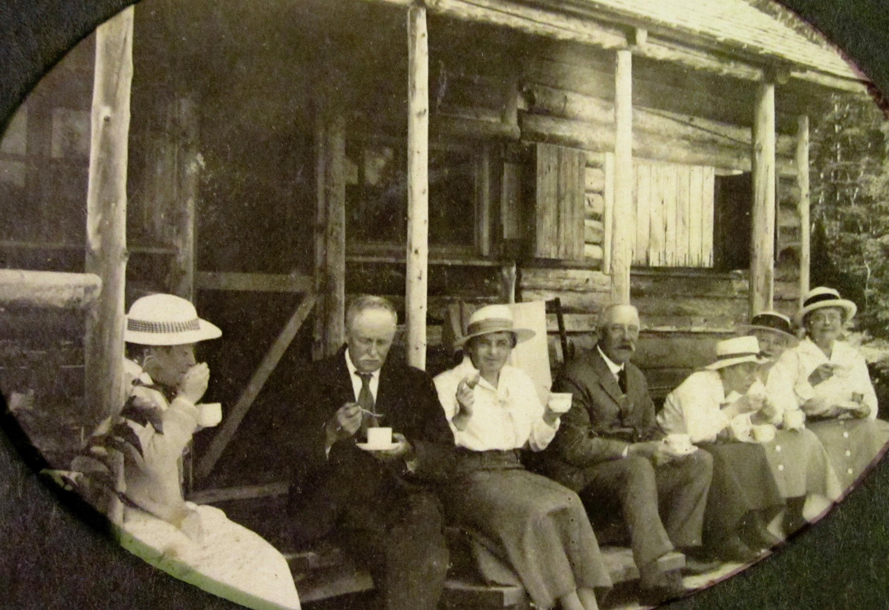 Des adultes d'âge mûr prennent le thé sur la galerie d'un camp très rustique.