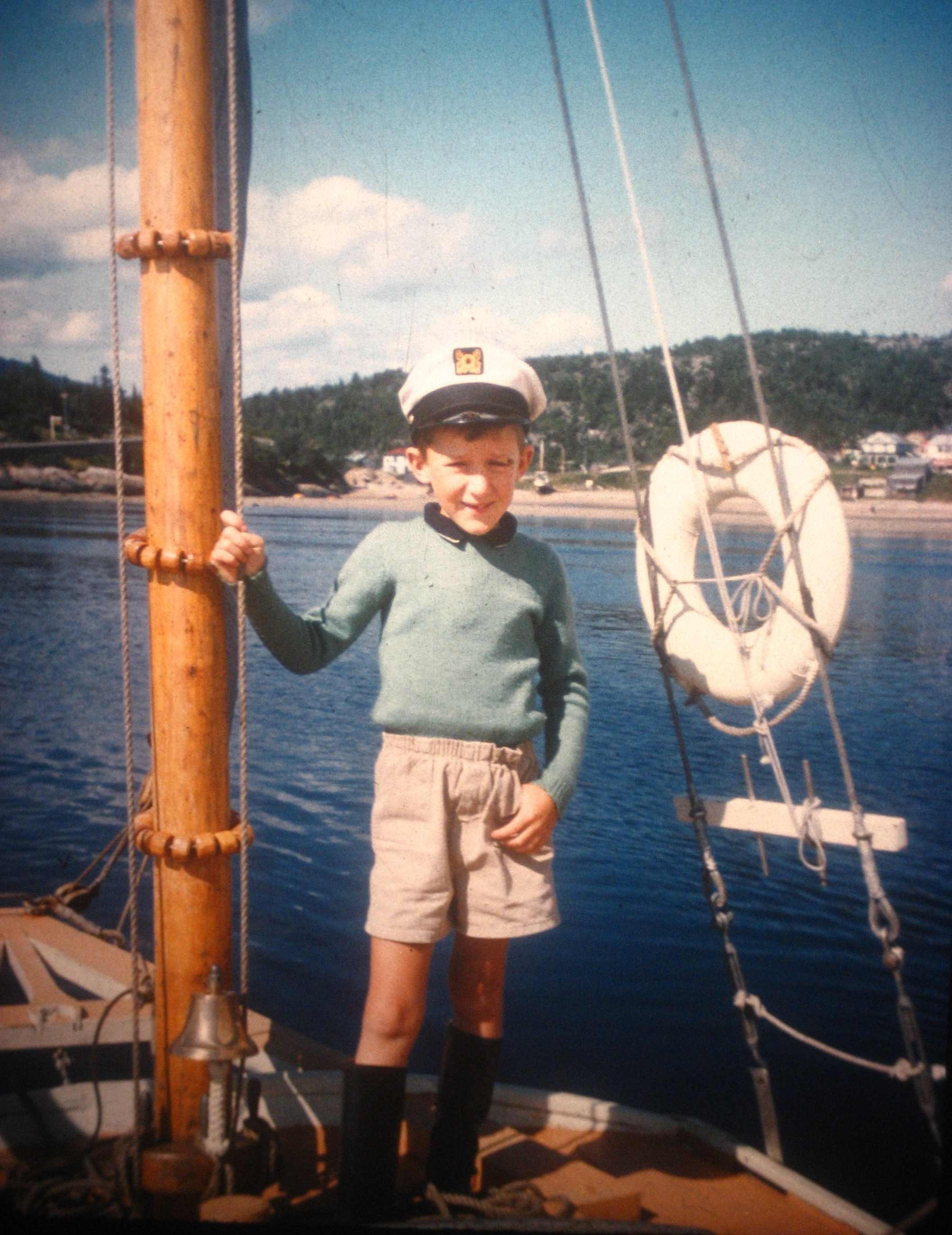 Un garçon se tient au mât d'un bateau de plaisance, non loin de la rive.